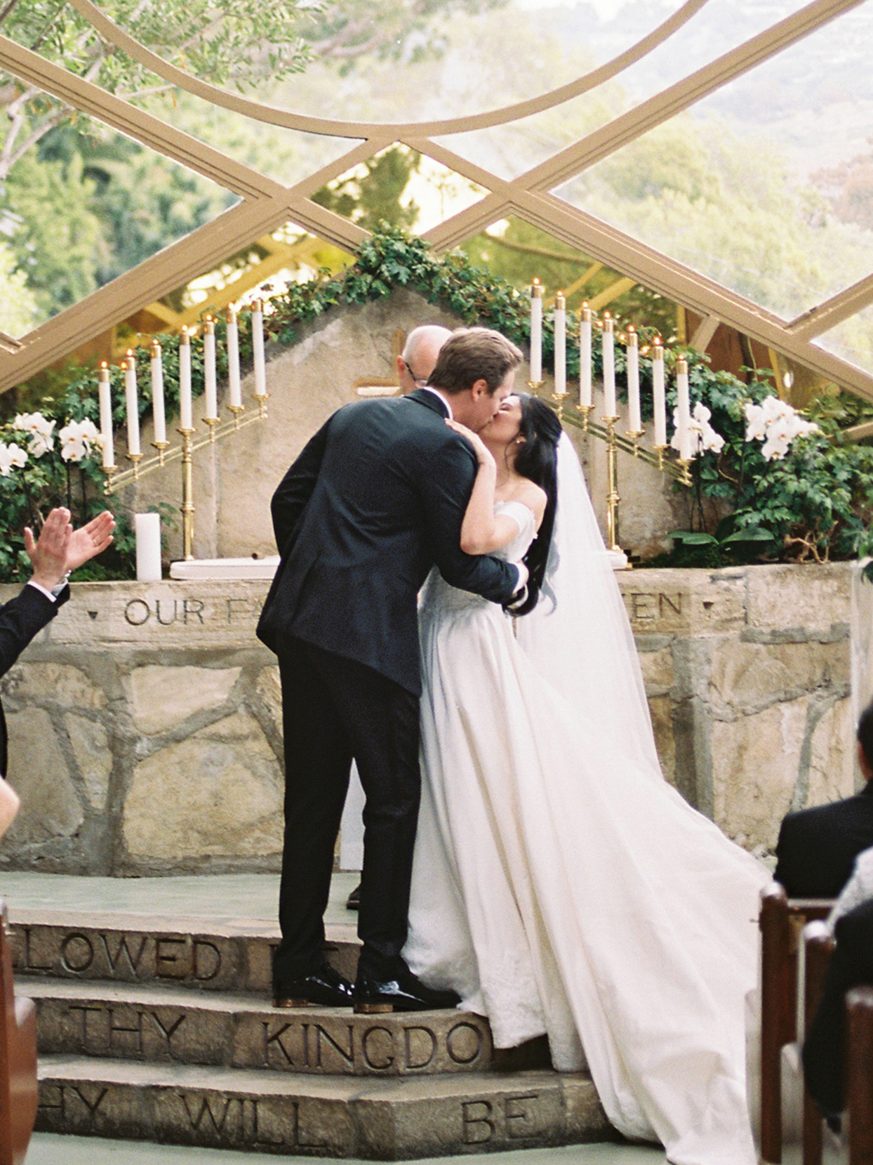 wedding couple first kiss on church steps at ceremony