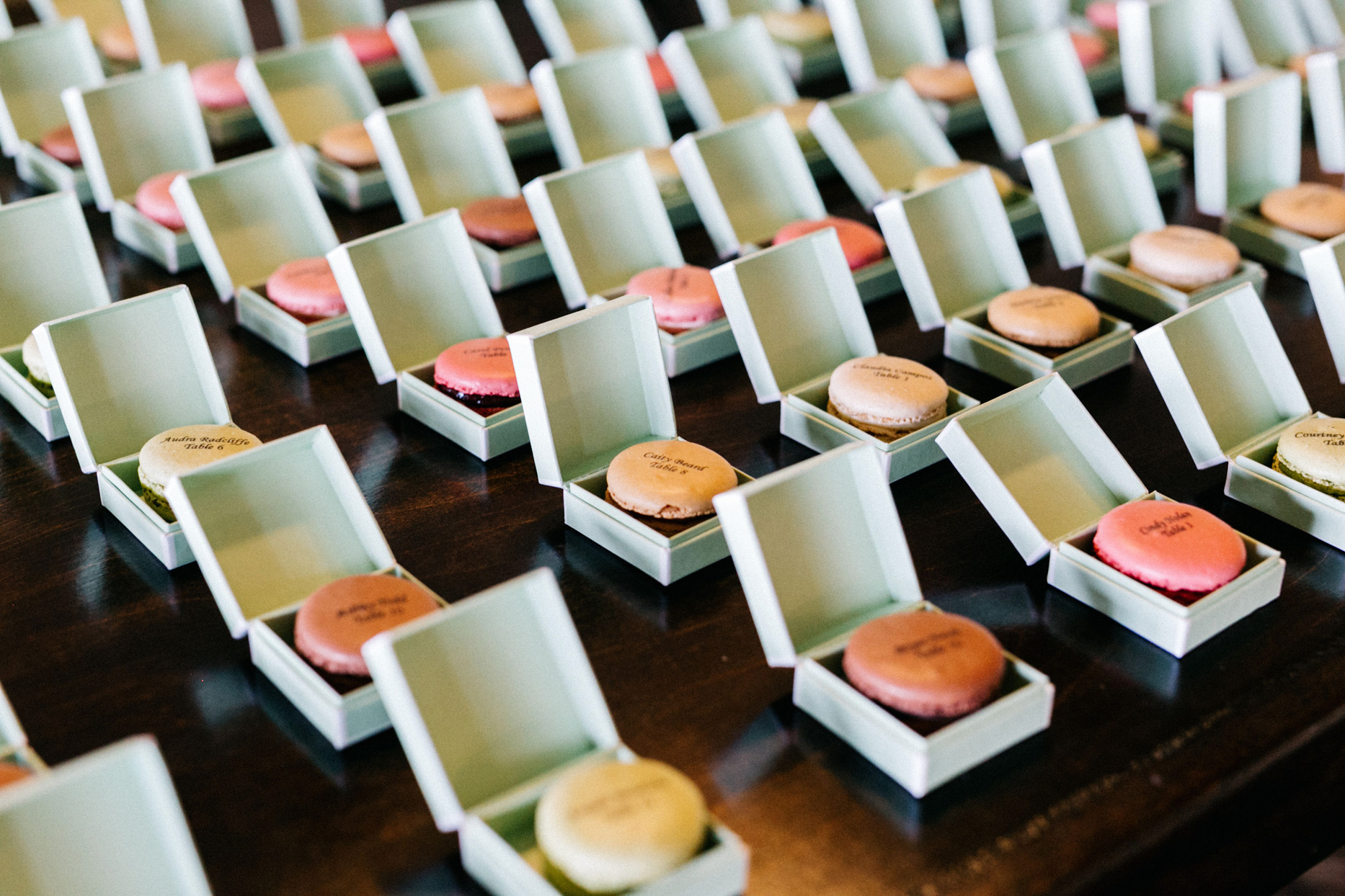 mint colored boxes with macaroons as reception seating chart