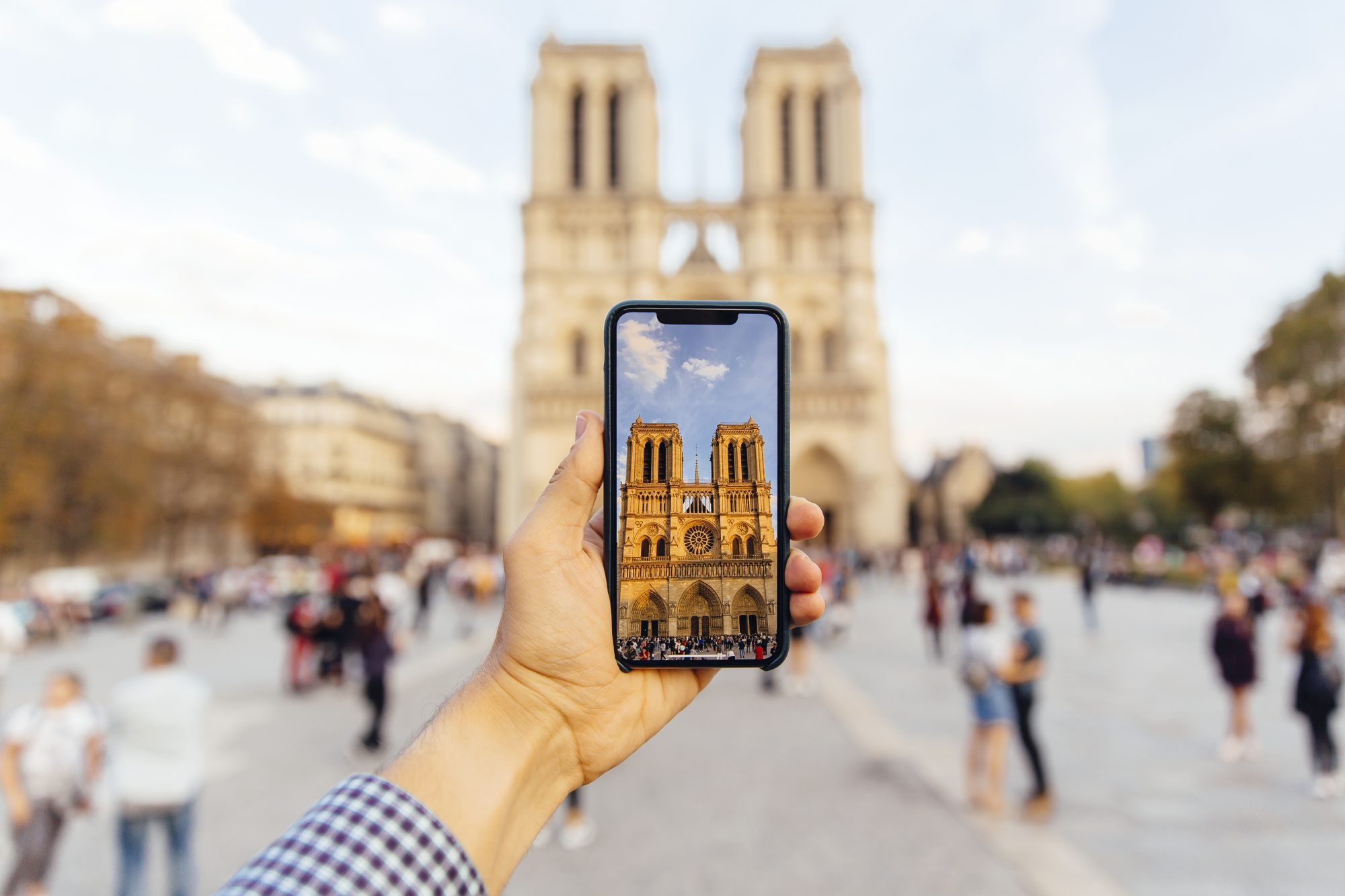tourist taking picture of Notre Dame cathedral with smart phone