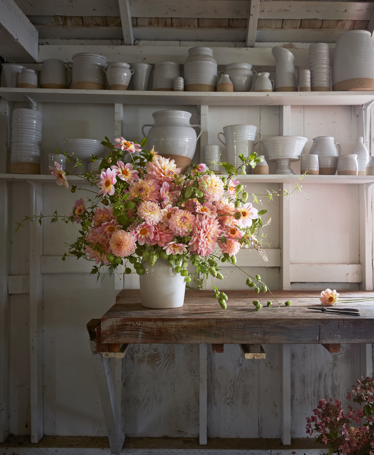 bright dahlia arrangement surrounded by pottery