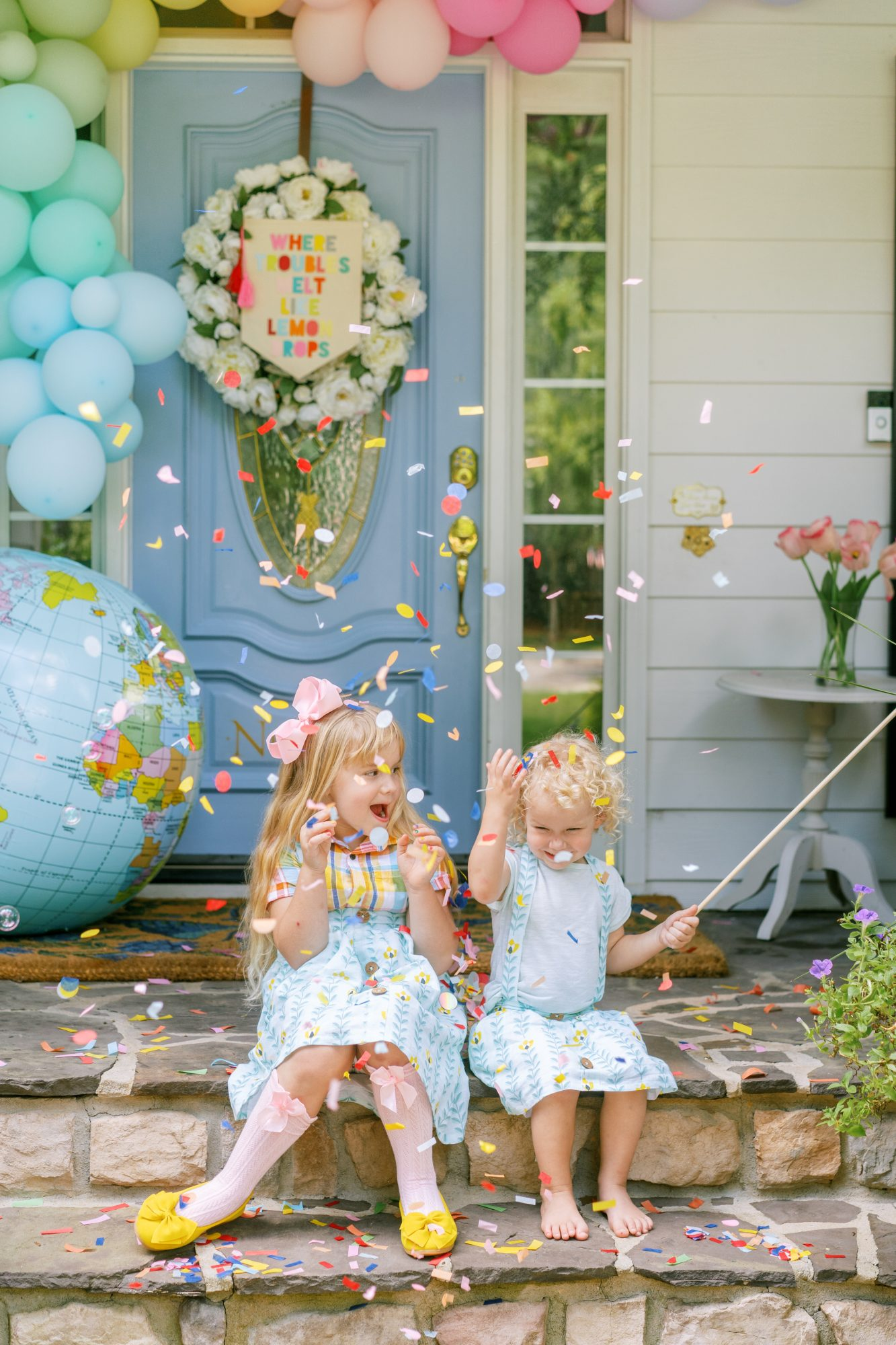 two girls sitting on porch throwing confetti