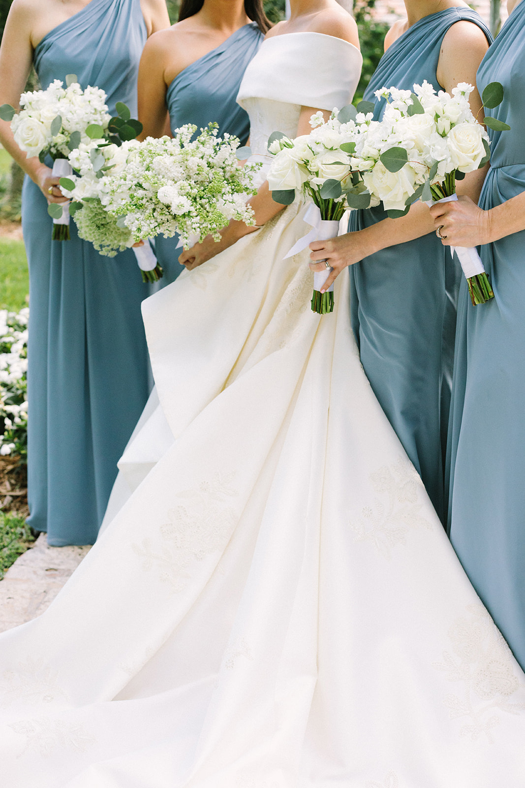 bride with bridesmaids holding white floral wedding bouquets