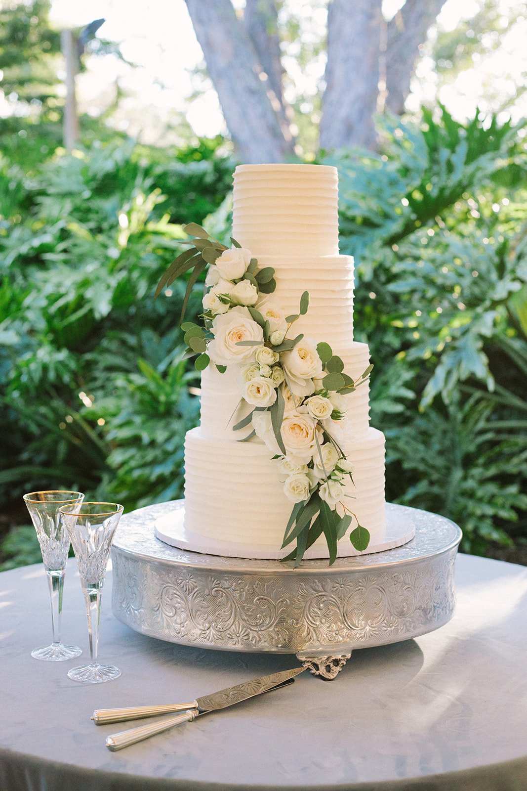 four tiered white frosted wedding cake with floral accent