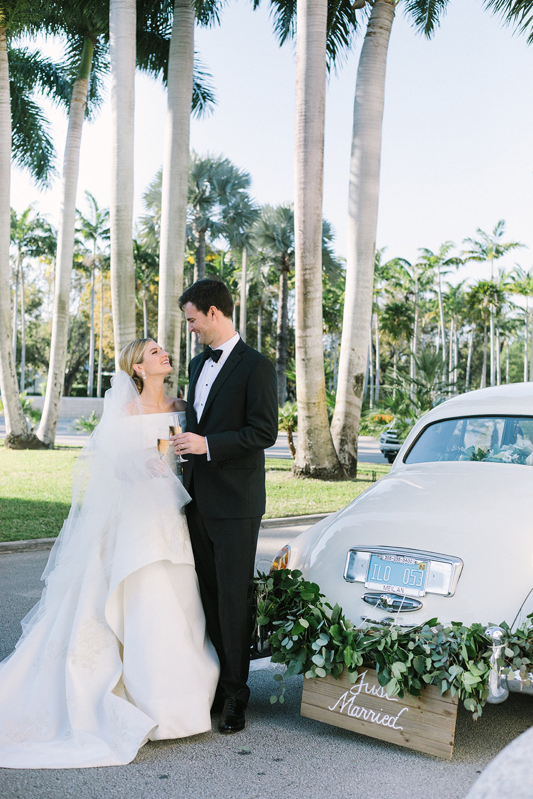 bride and groom smiling standing next to white vintage car