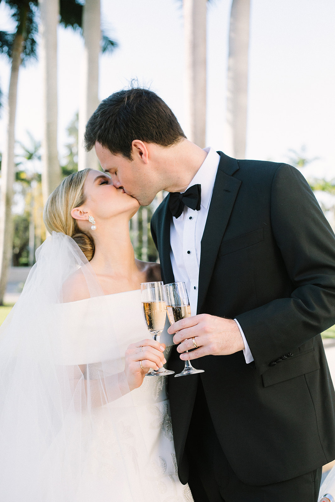 bride and groom kissing holding champagne flutes