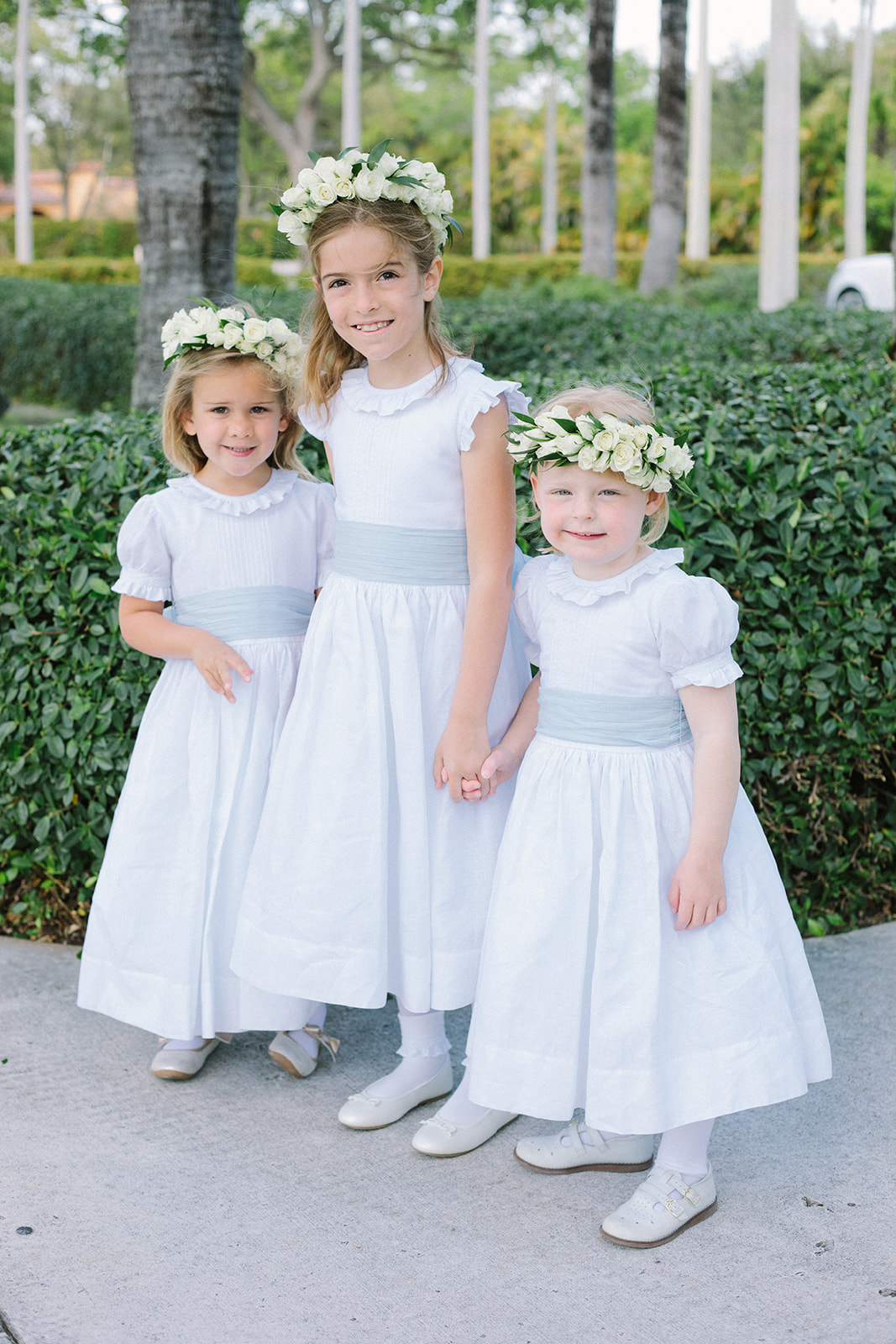 three flower girls wearing white dresses and flower crowns