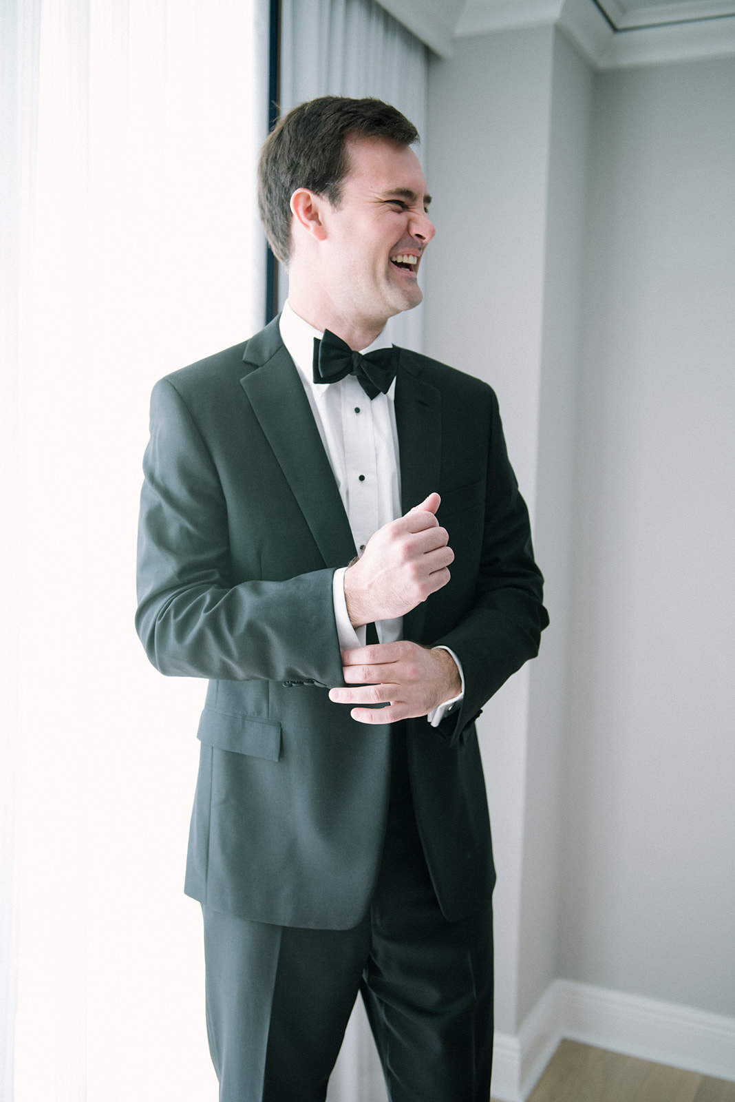 groom smiling in classic black and white tux
