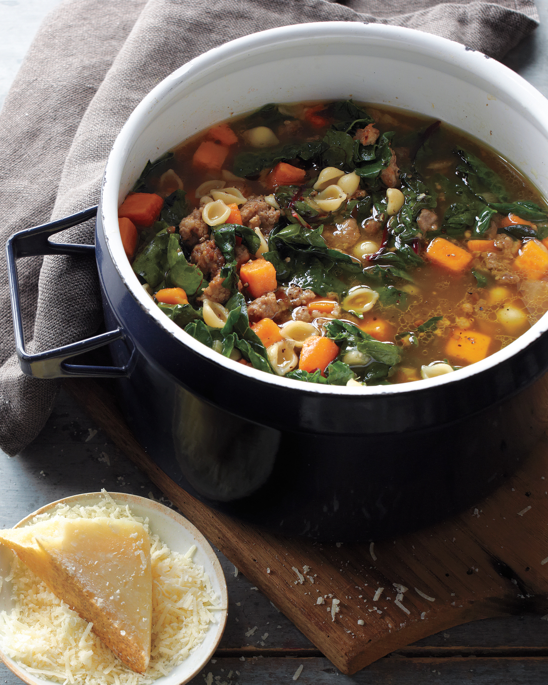 Sweet Potato-Sausage Soup in Dutch oven with dish of Parmesan