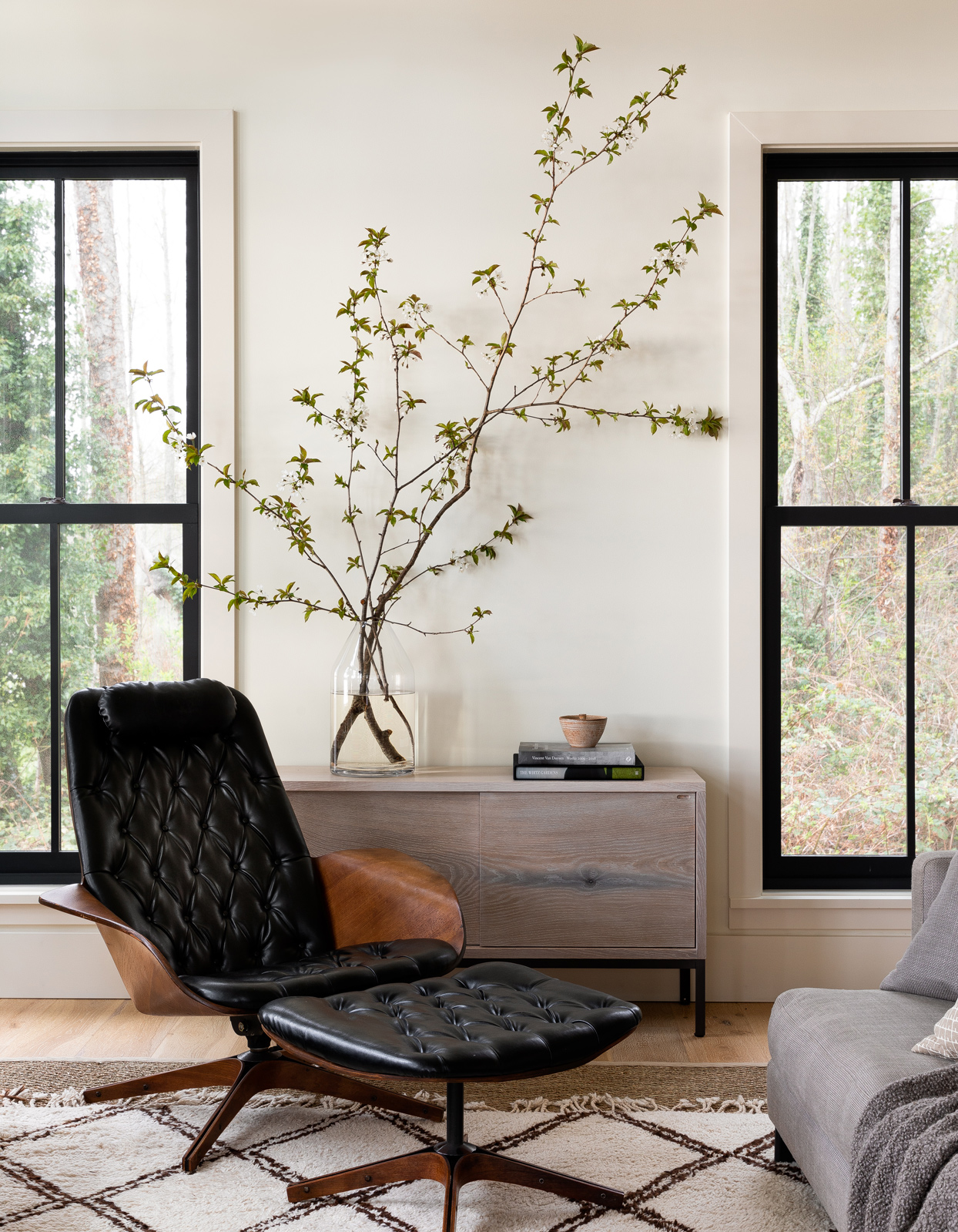 living room with black leather chair and tall floral branches