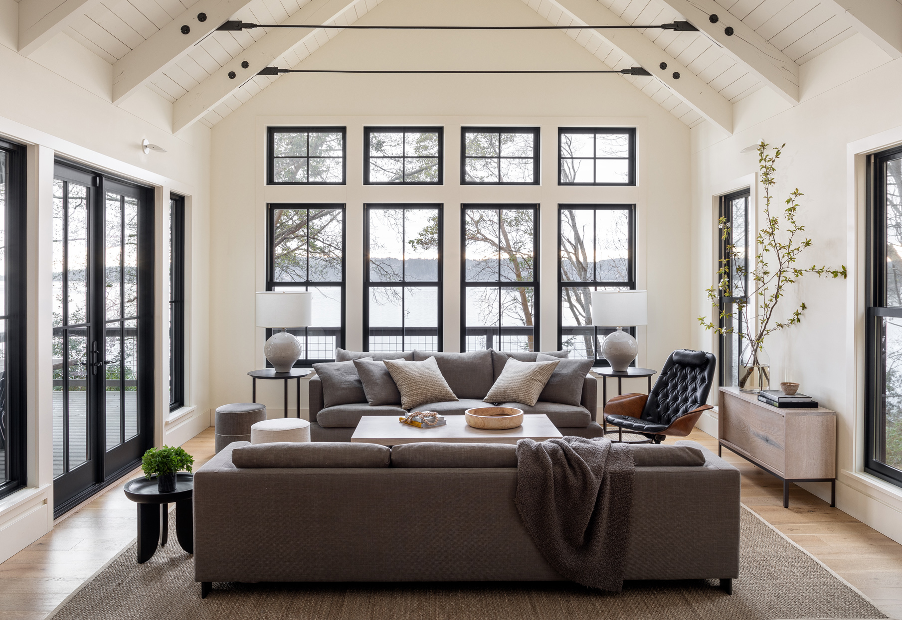 neutral-colored living room with windows overlooking lake