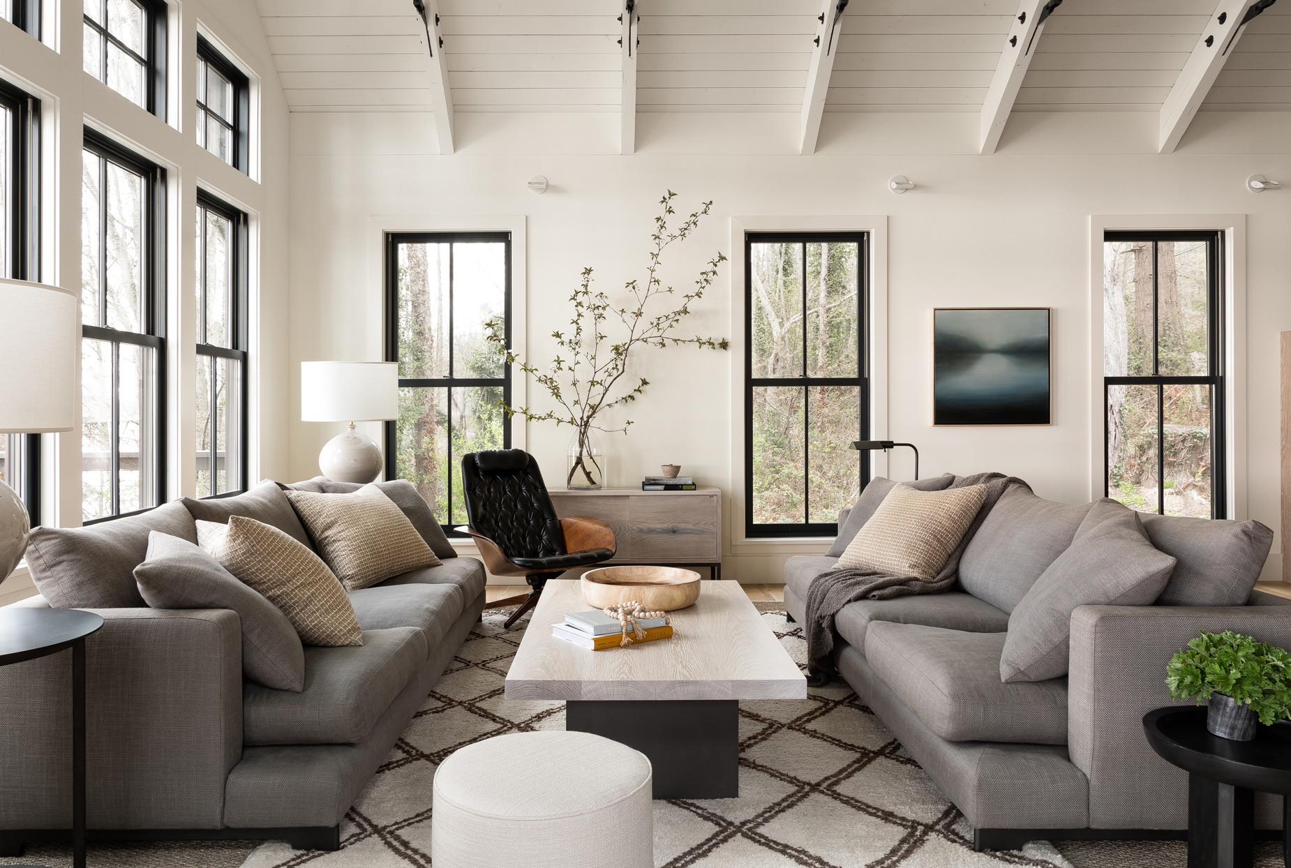 neutral-colored living room with greenery accents and vaulted ceiling