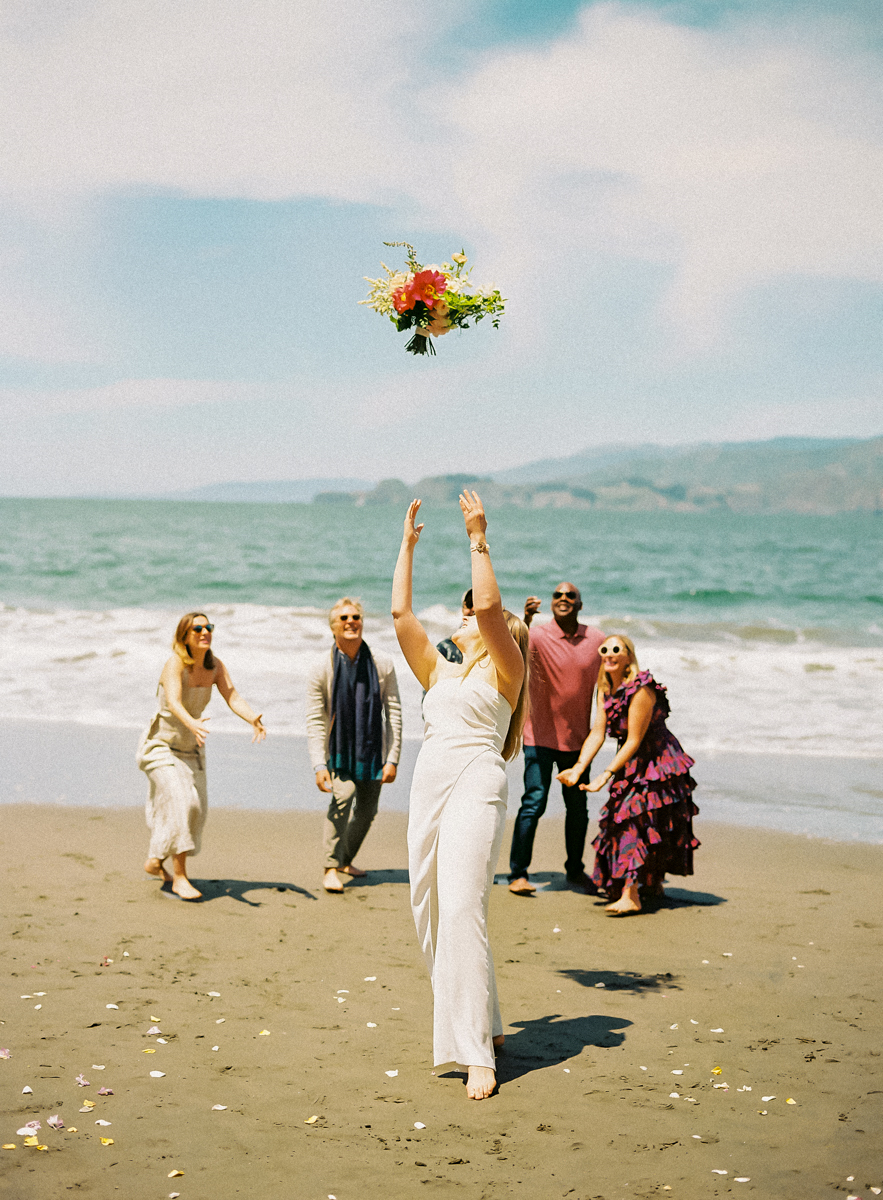 bride throwing her bouquet on the beach