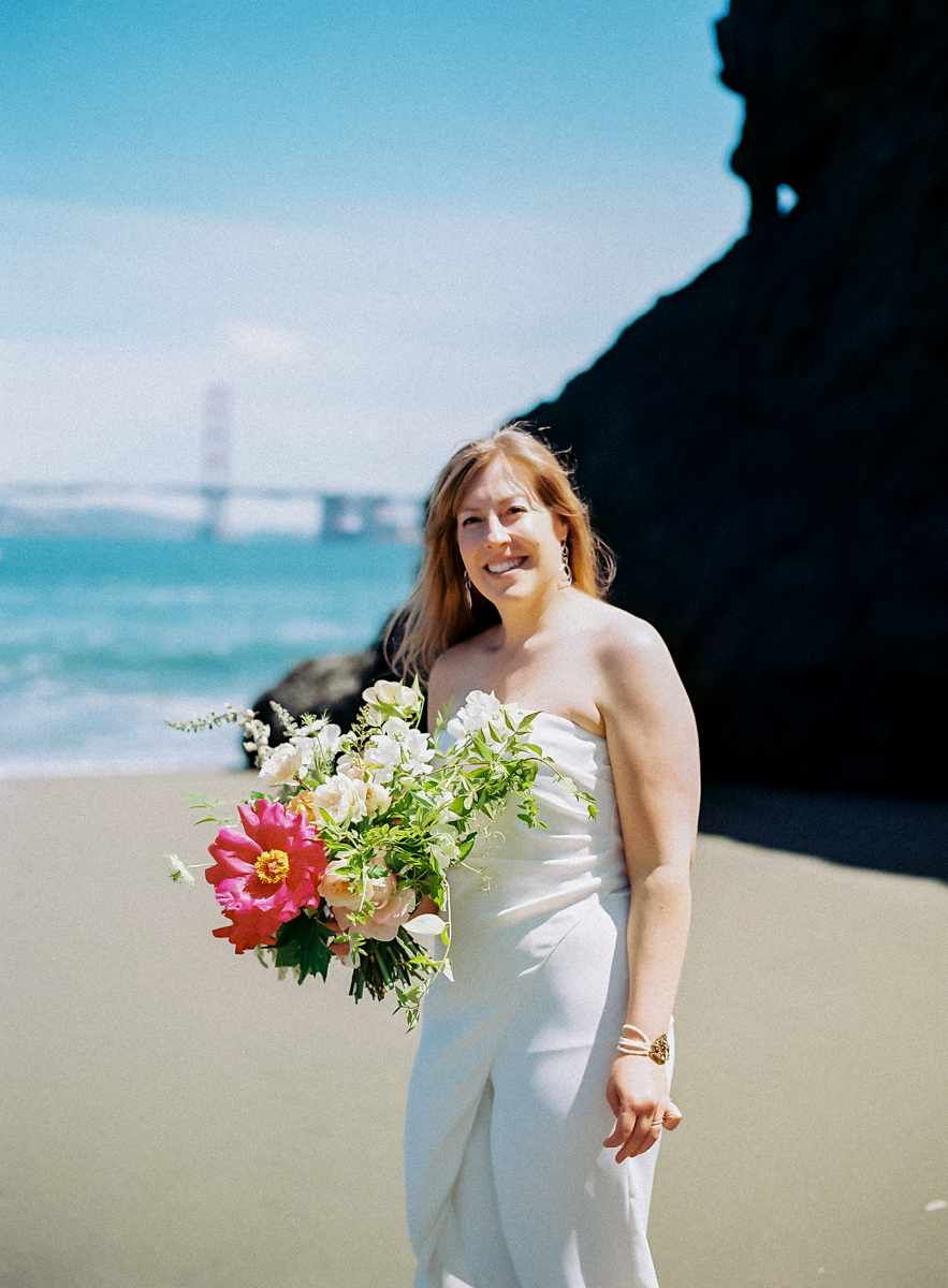 bride holding her bouquet on the beach