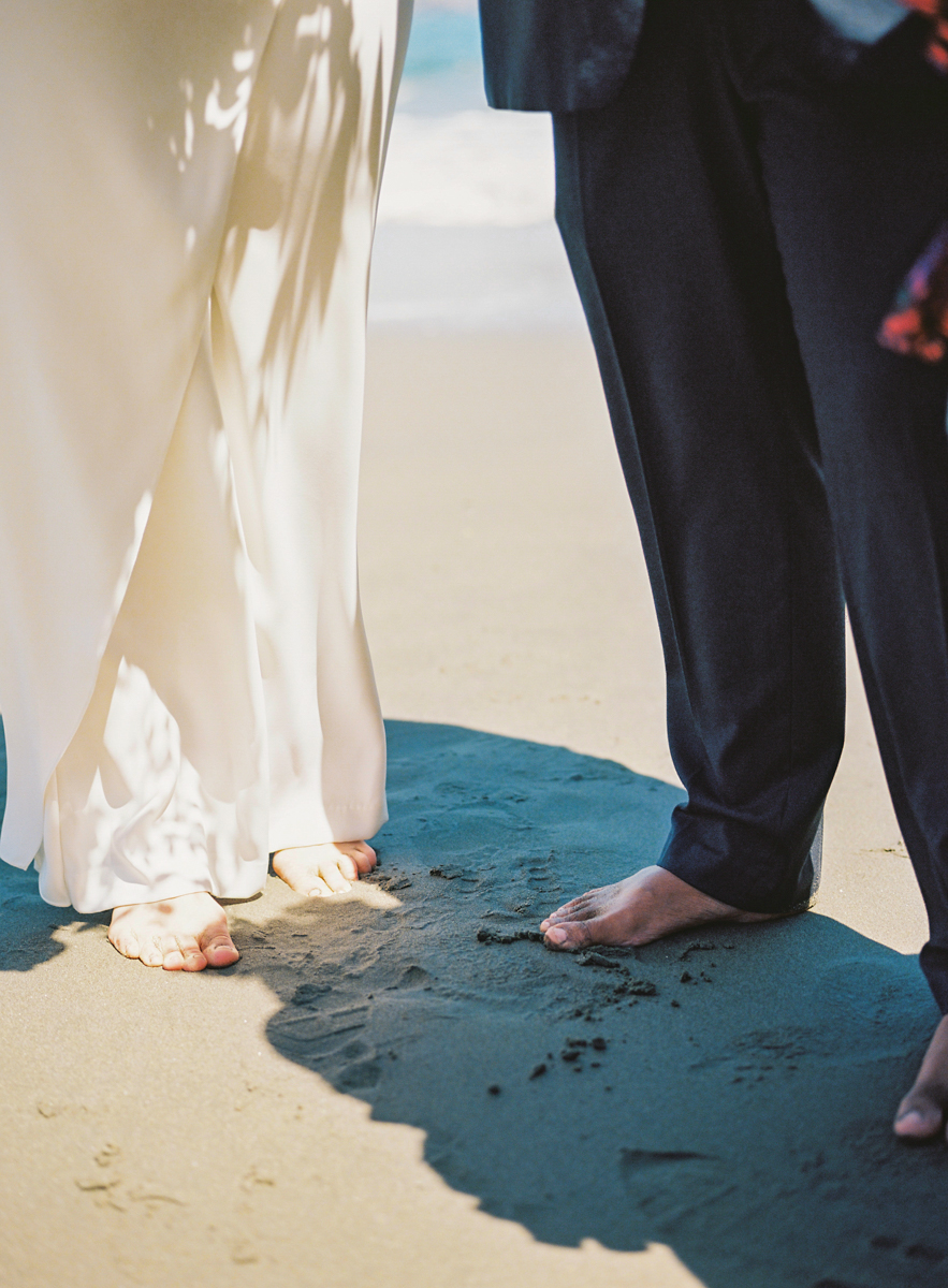 bride and groom feet in the sand