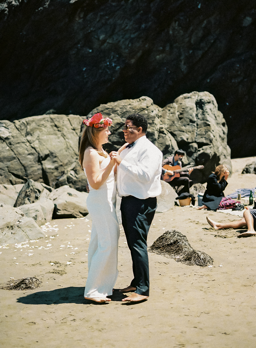 bride and groom sharing first dance on the beach
