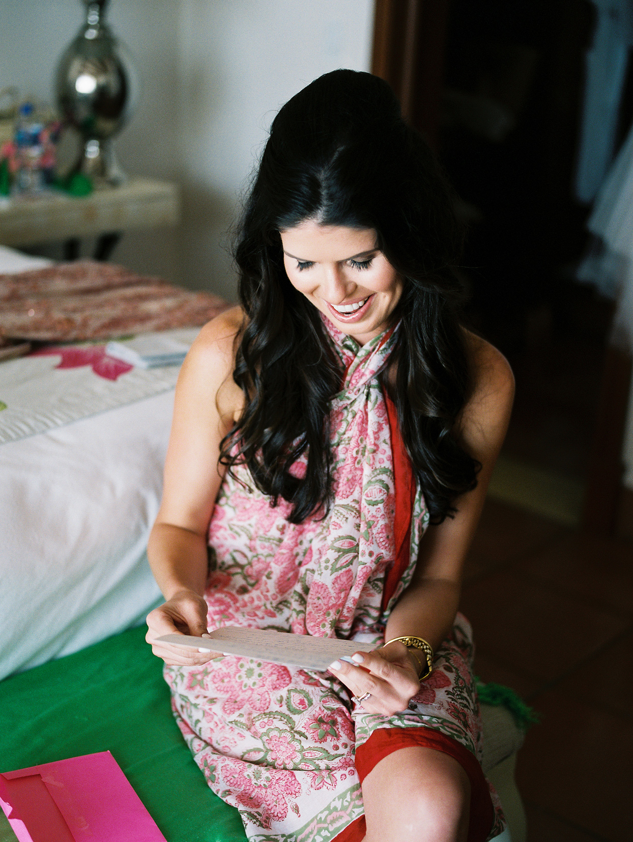 bride smiling while reading card before getting ready