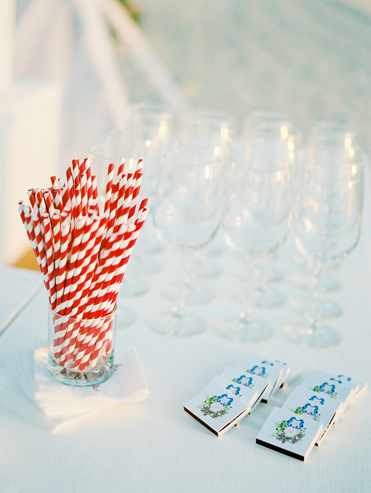 red and white striped straws next to clear wine glasses and custom matchbooks