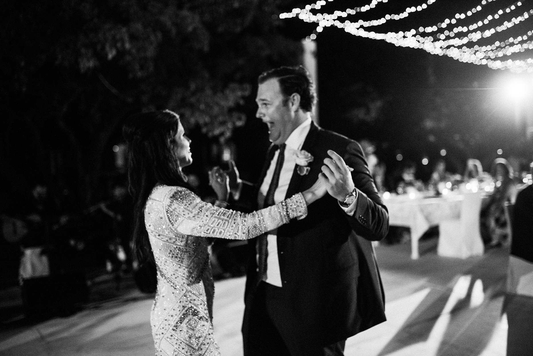 groom smiles boldly at bride during reception dance