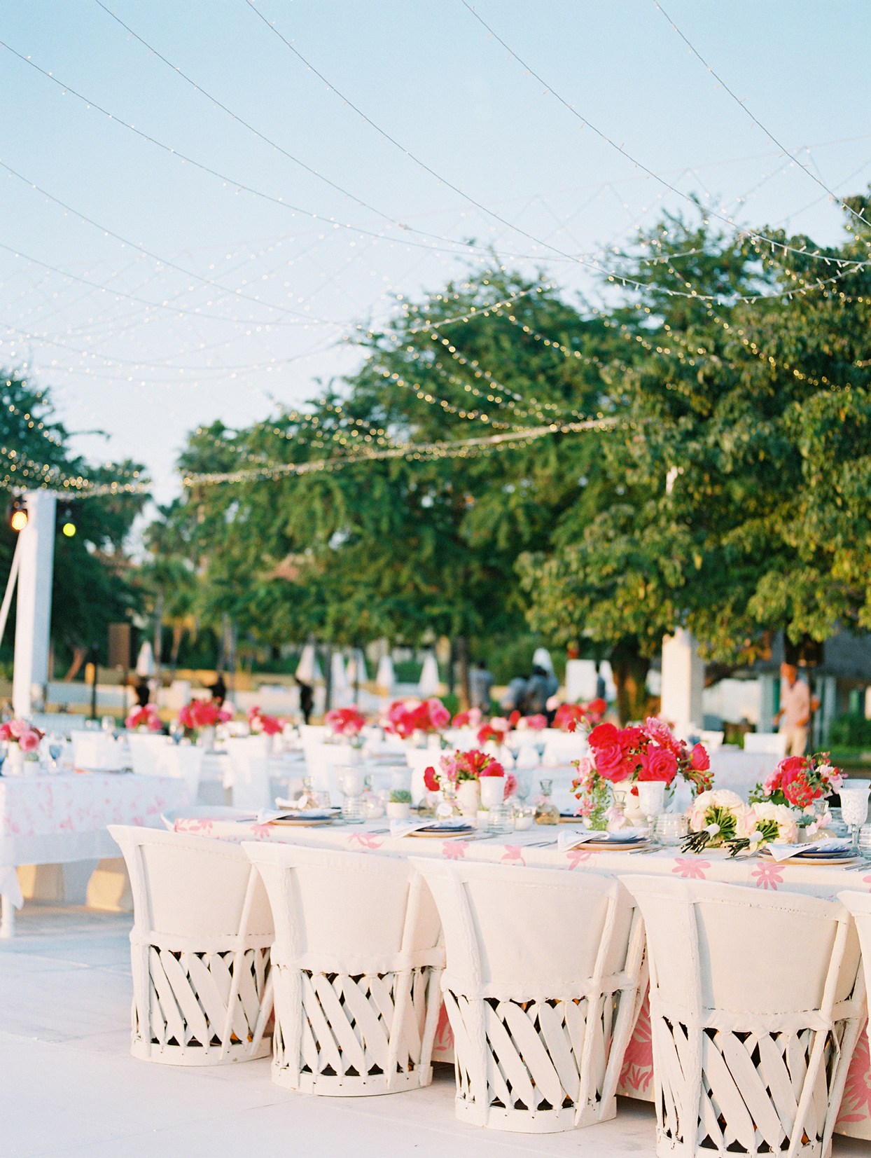 long reception tables under string lights outside