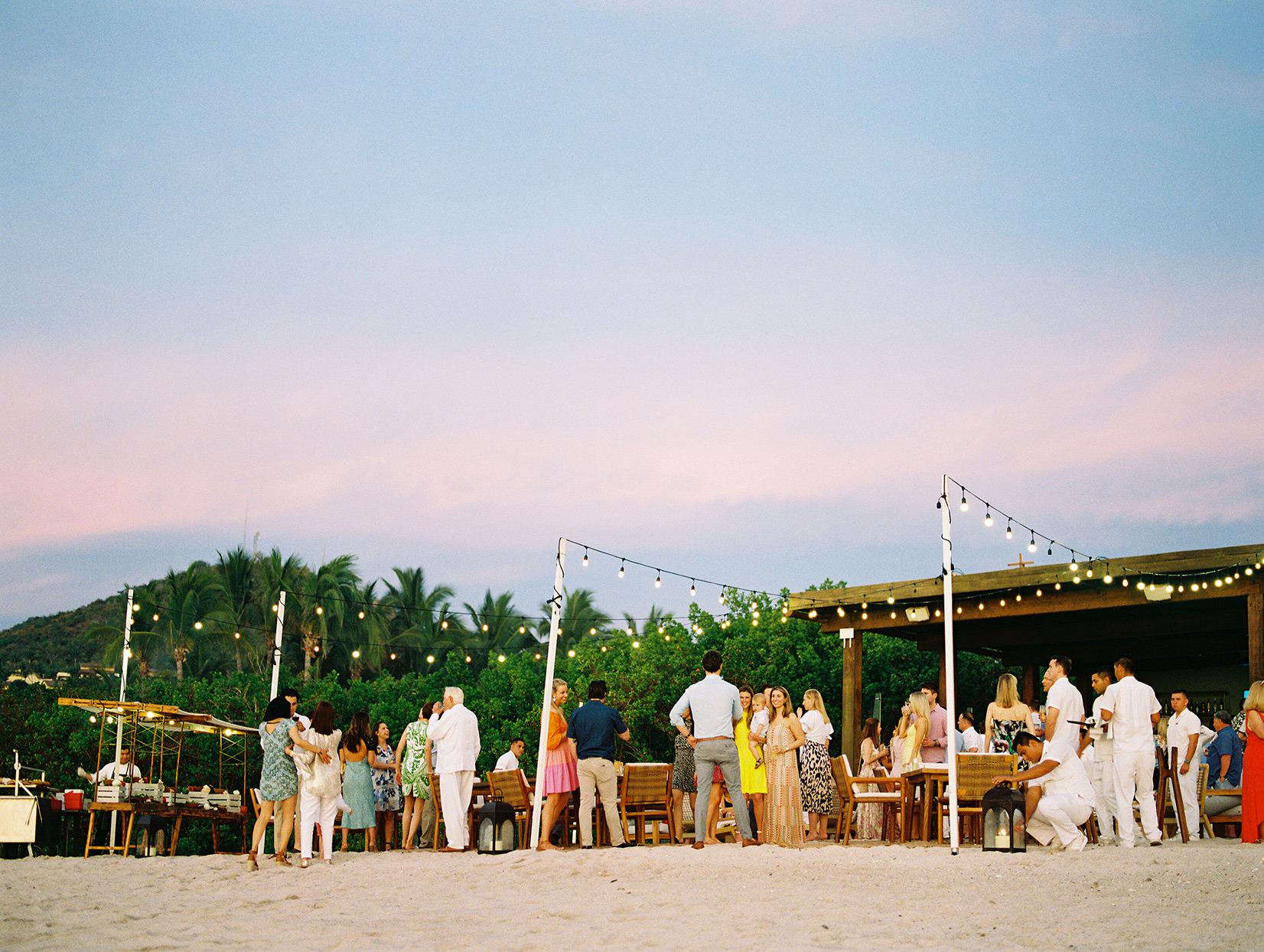 guests gathered outside on beach for welcome party