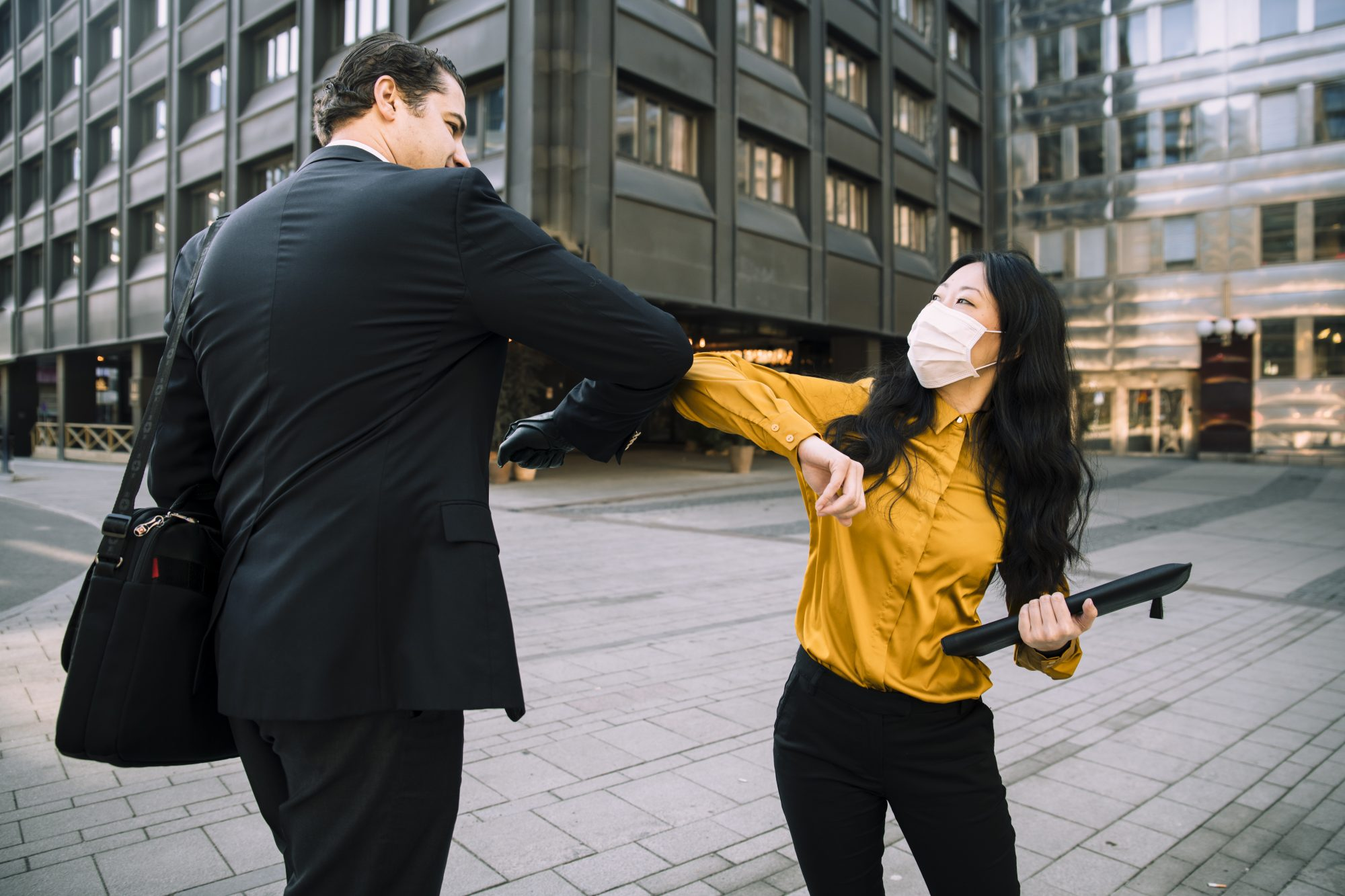 two people bumping elbows as greeting