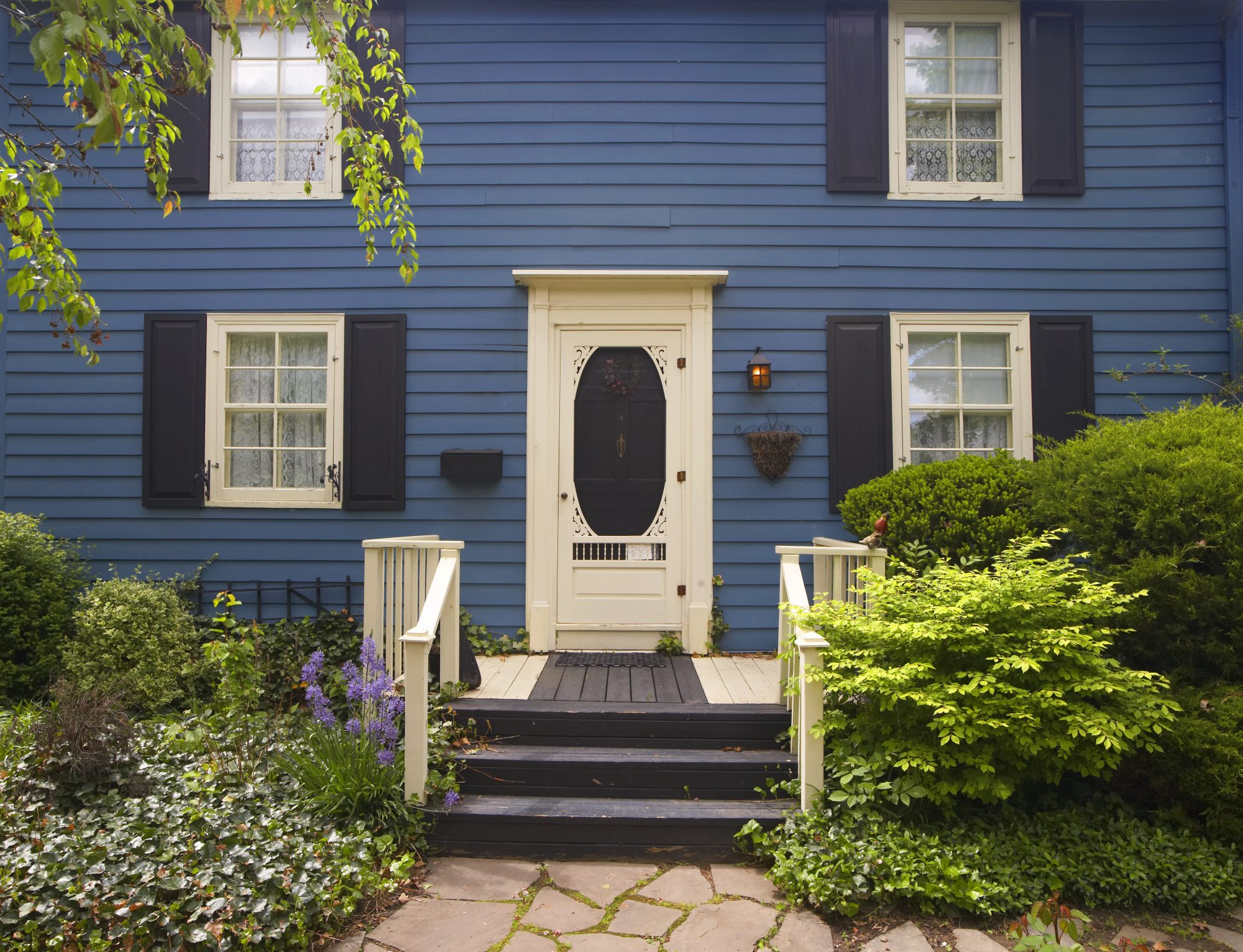 pretty blue house with cream door and black shutters