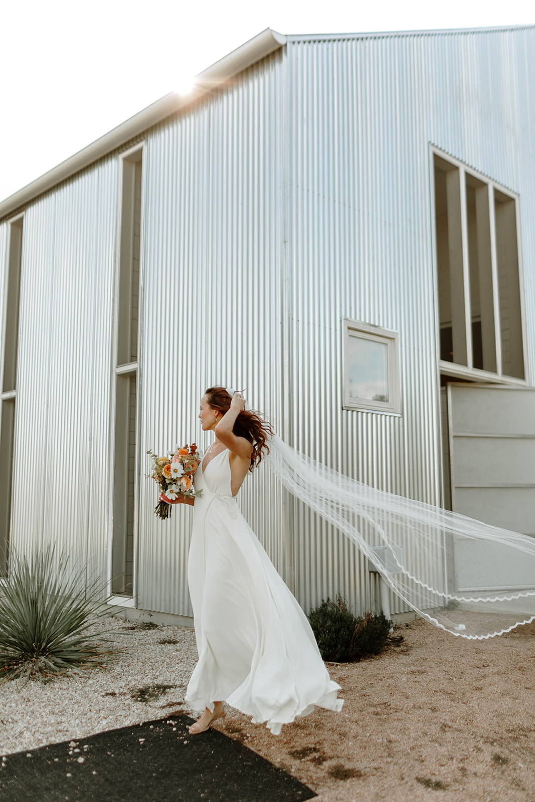bride wearing long vail with light flowing wedding dress