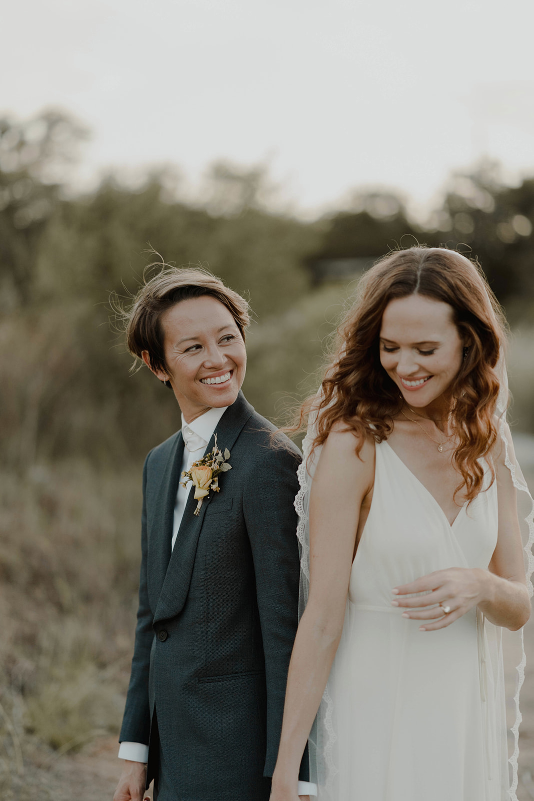 bride smiling at one another outside