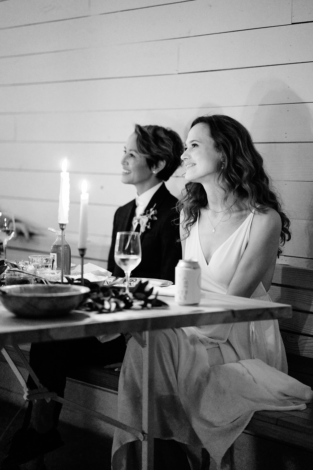 brides smiling sitting at table during reception