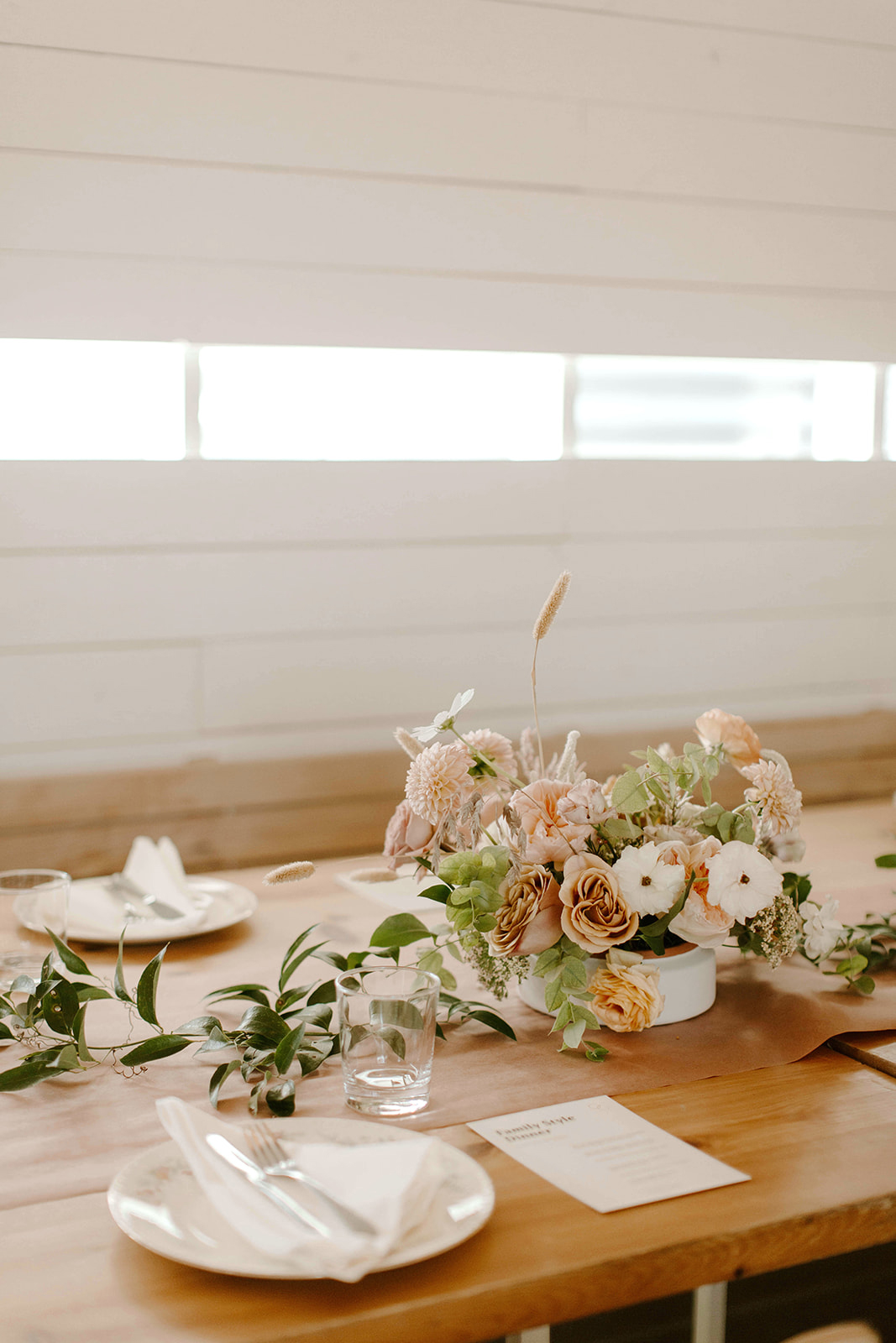 minimal reception table setting with greenery and floral centerpieces
