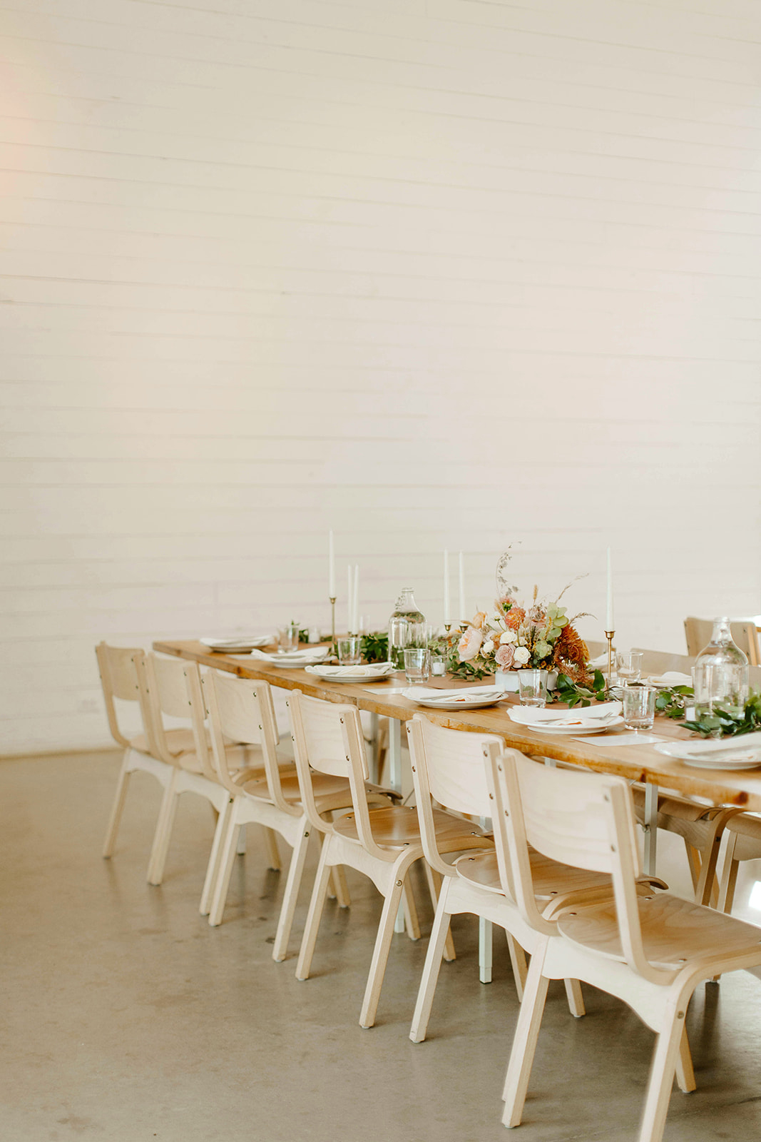 long wooden tables with light tan wood chairs reception set up