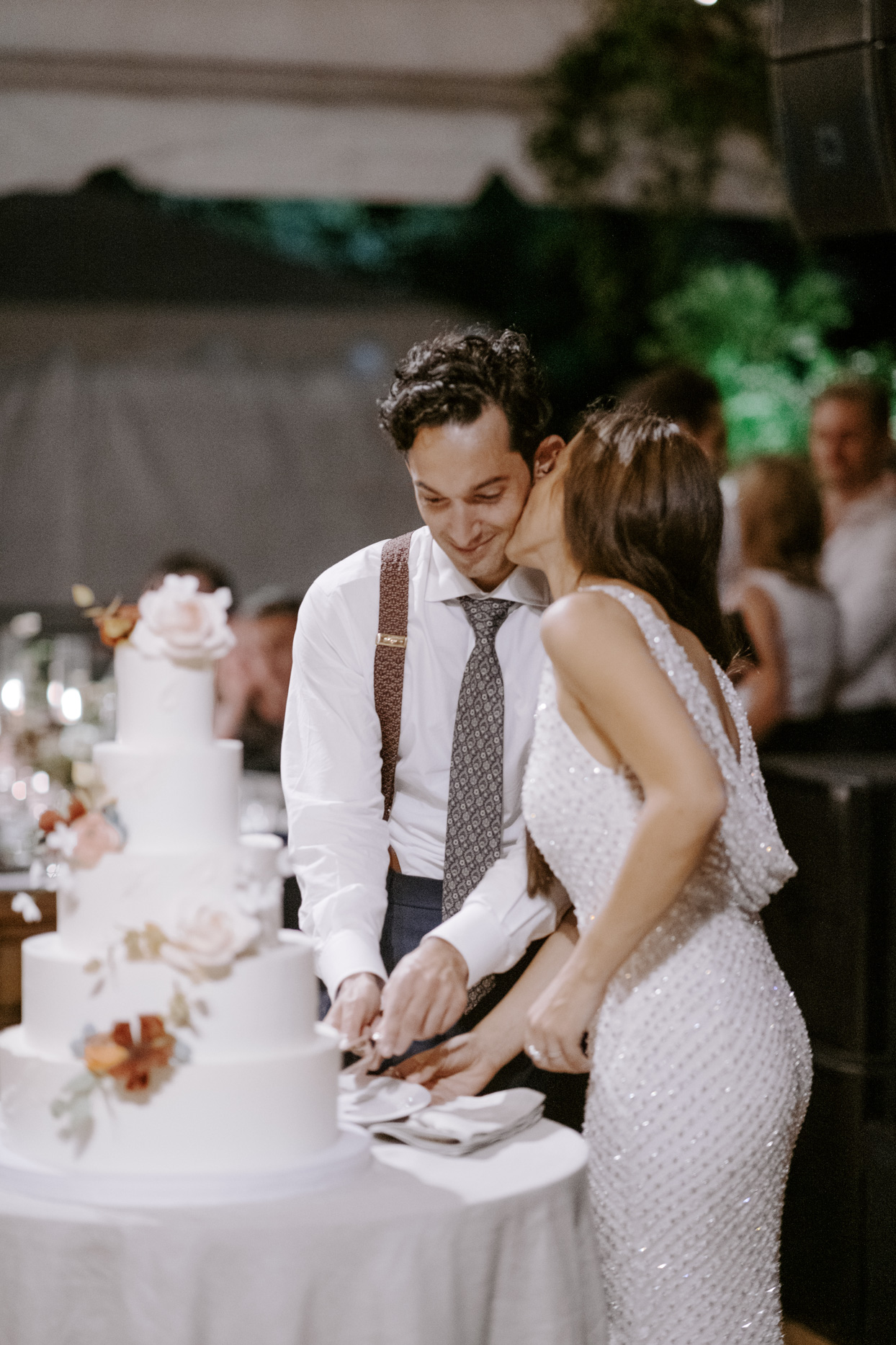 bride kissing groom during cake cutting at reception