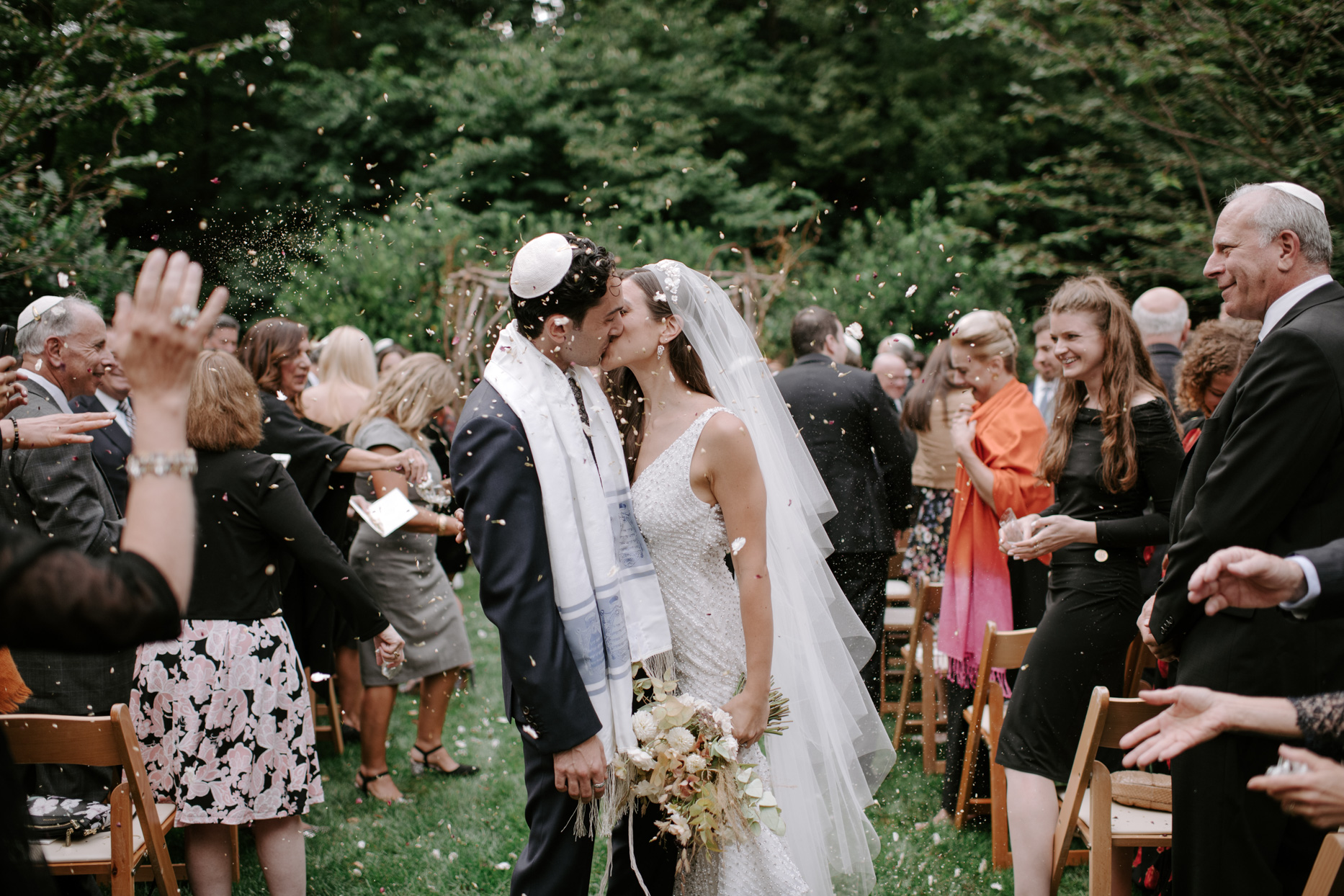 bride and groom kissing during recessional showered in flower petals