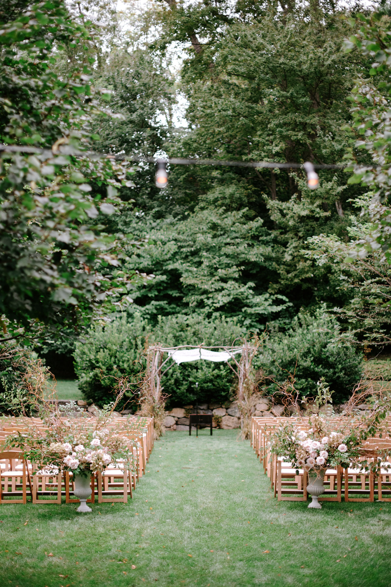 outdoor ceremony set up with wooden chairs and chuppah