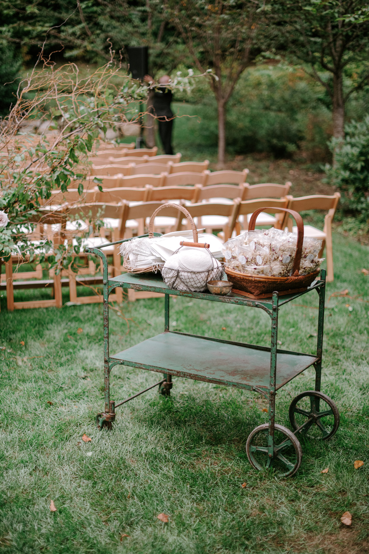 antique rustic cart sitting at outdoor ceremony with yarmulkes and petals