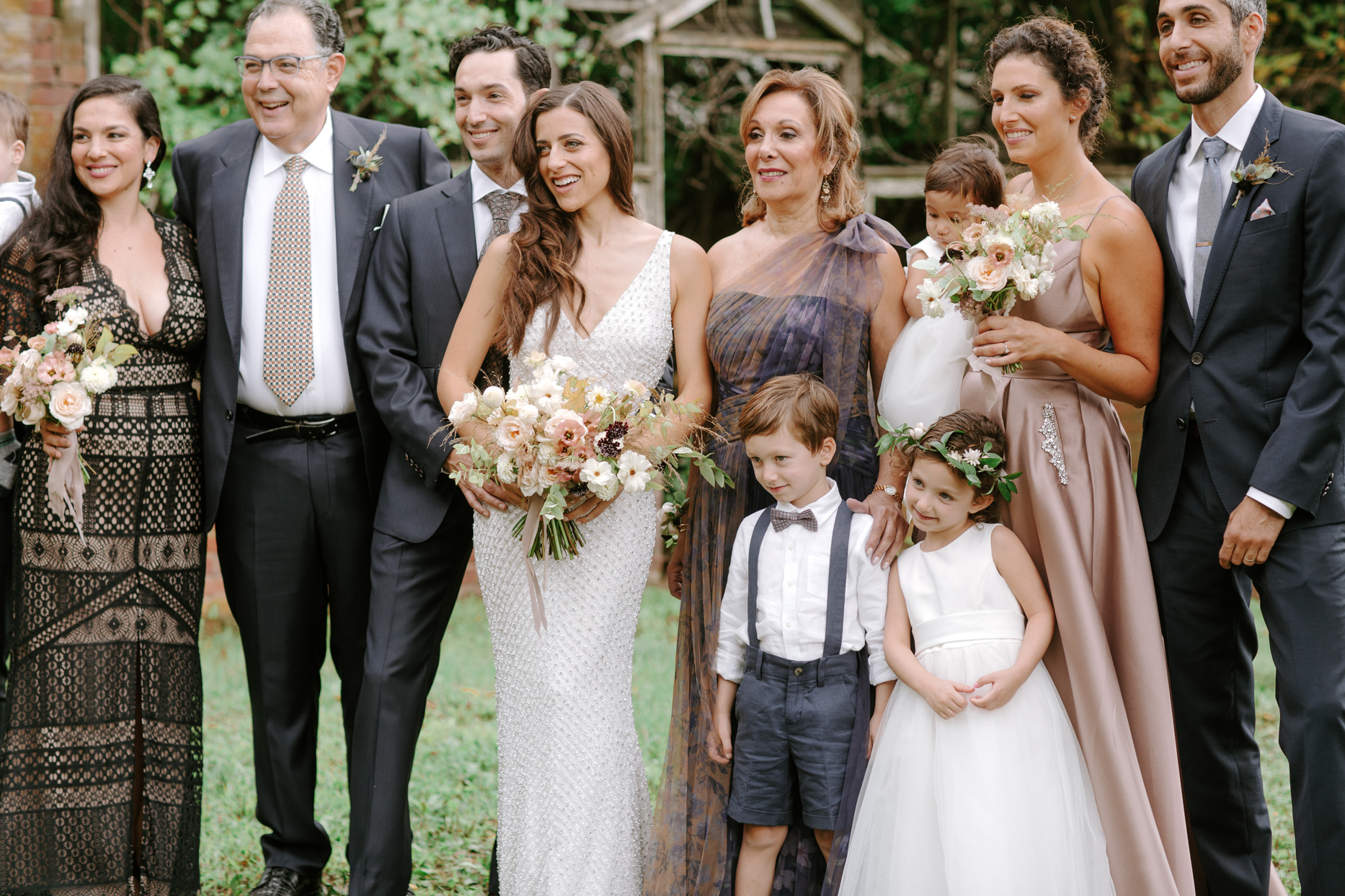wedding couple posing with family in neutral tones