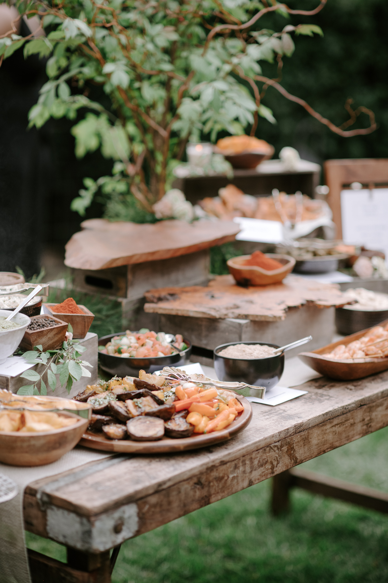 rustic wooden table with trays of wedding food