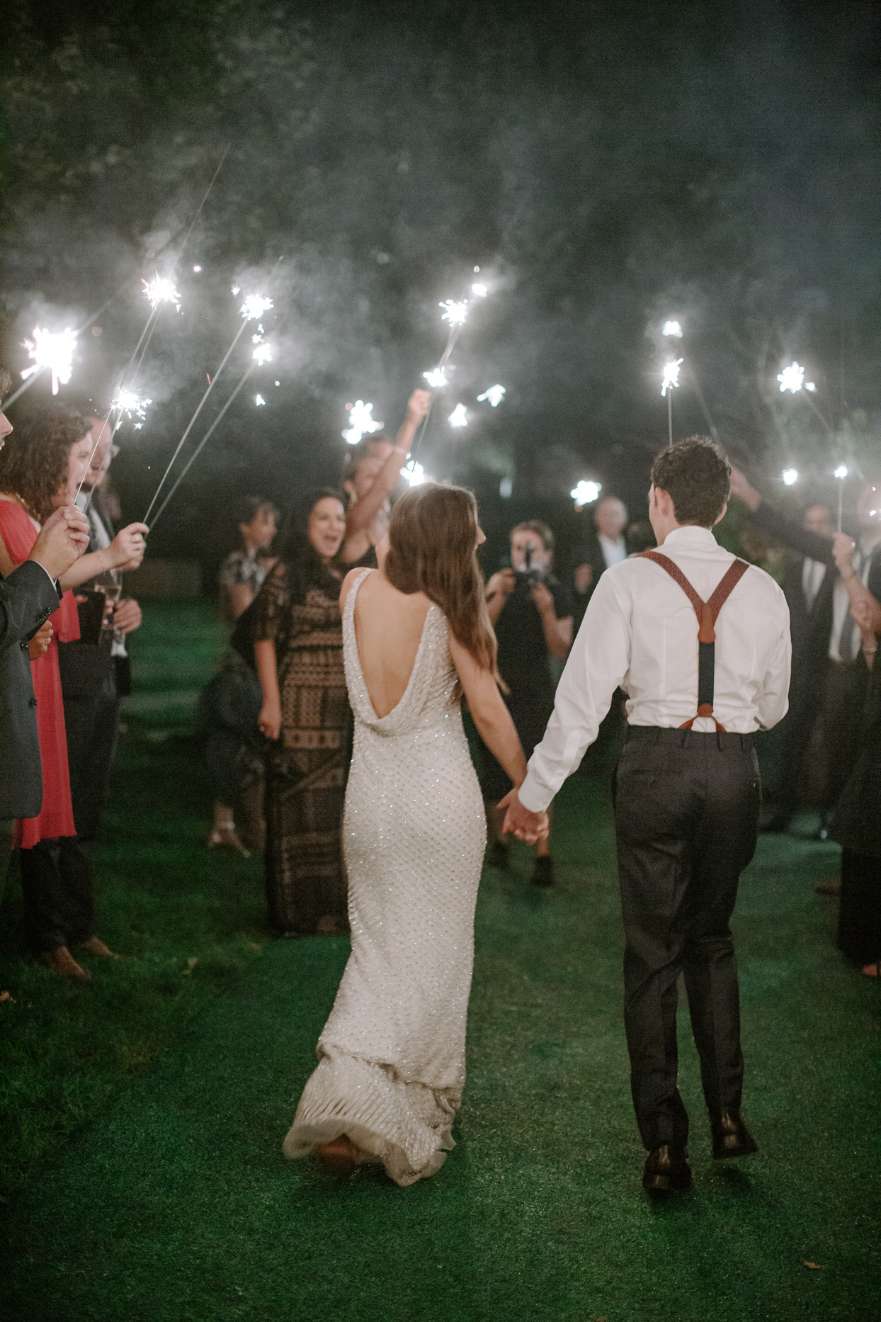 wedding couple existing while guests hold sparklers