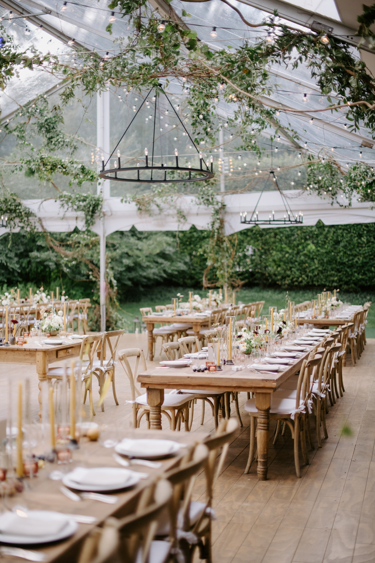 outdoor wedding reception in tent with wooden floor and tables