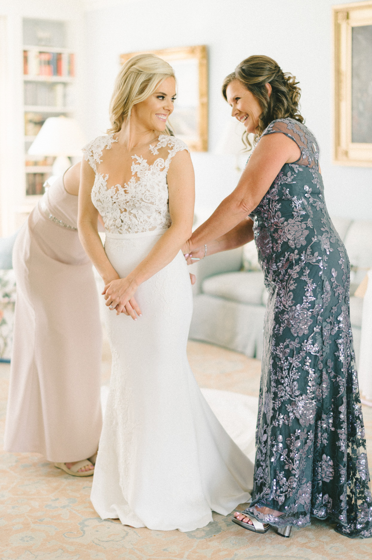 bride smiling as family helps her put on wedding dress