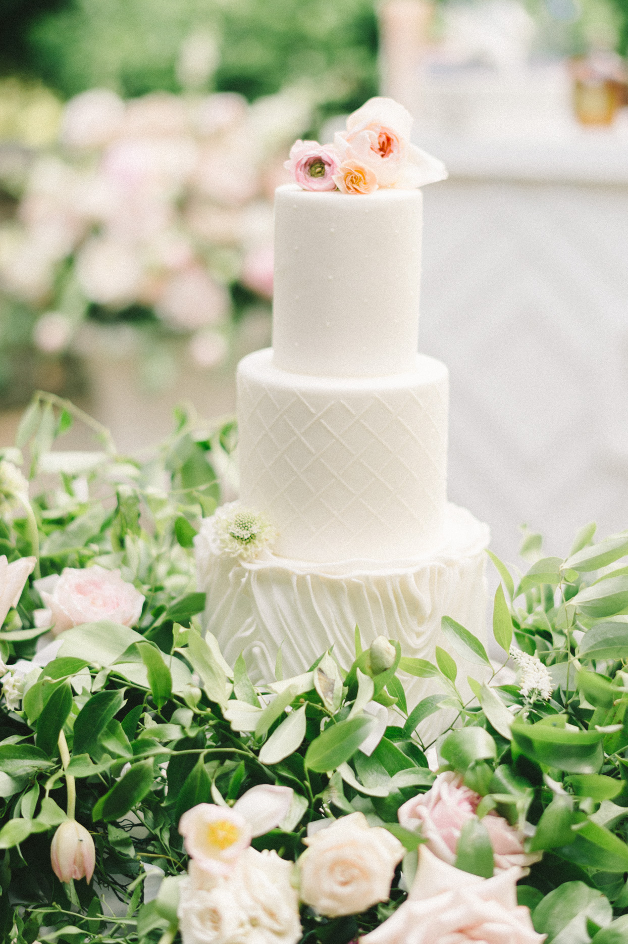 three tier white wedding cake with flowers and greenery