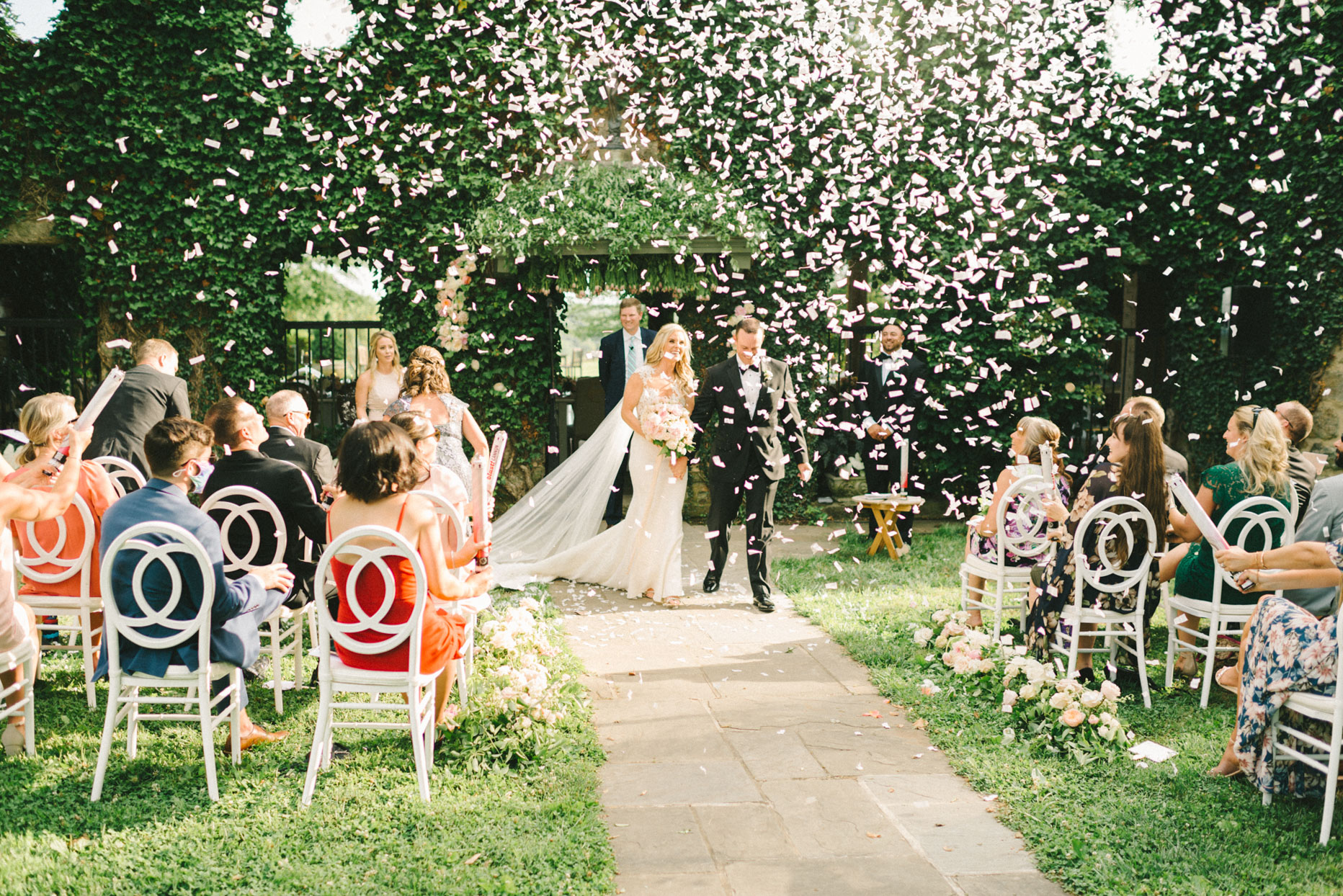 bride and groom exiting wedding ceremony in shower of confetti