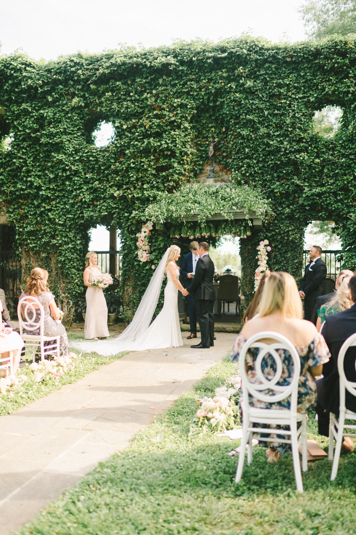 wedding ceremony couple holding hands in front of hedge wall