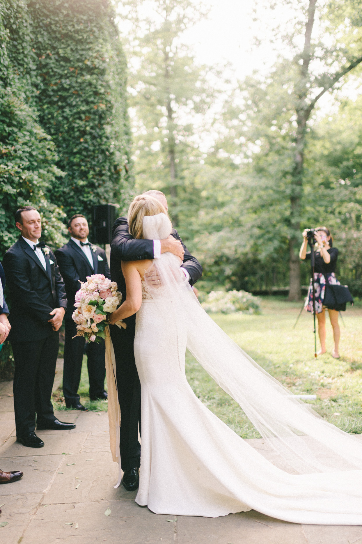 bride hugging father during outdoor ceremony