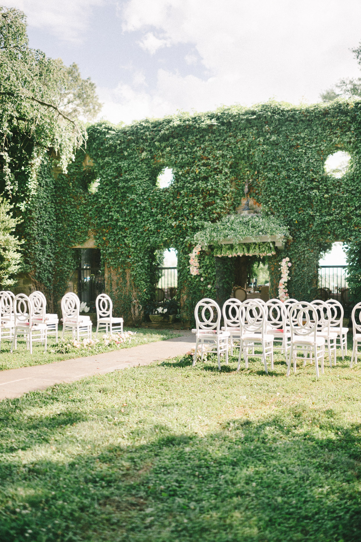 wedding ceremony set up on lawn against hedge wall