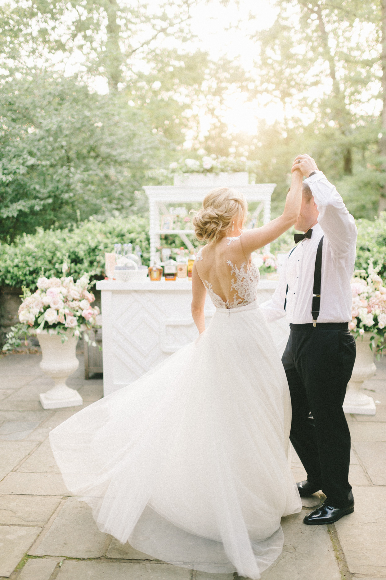 couple dancing on stone patio in front of bar