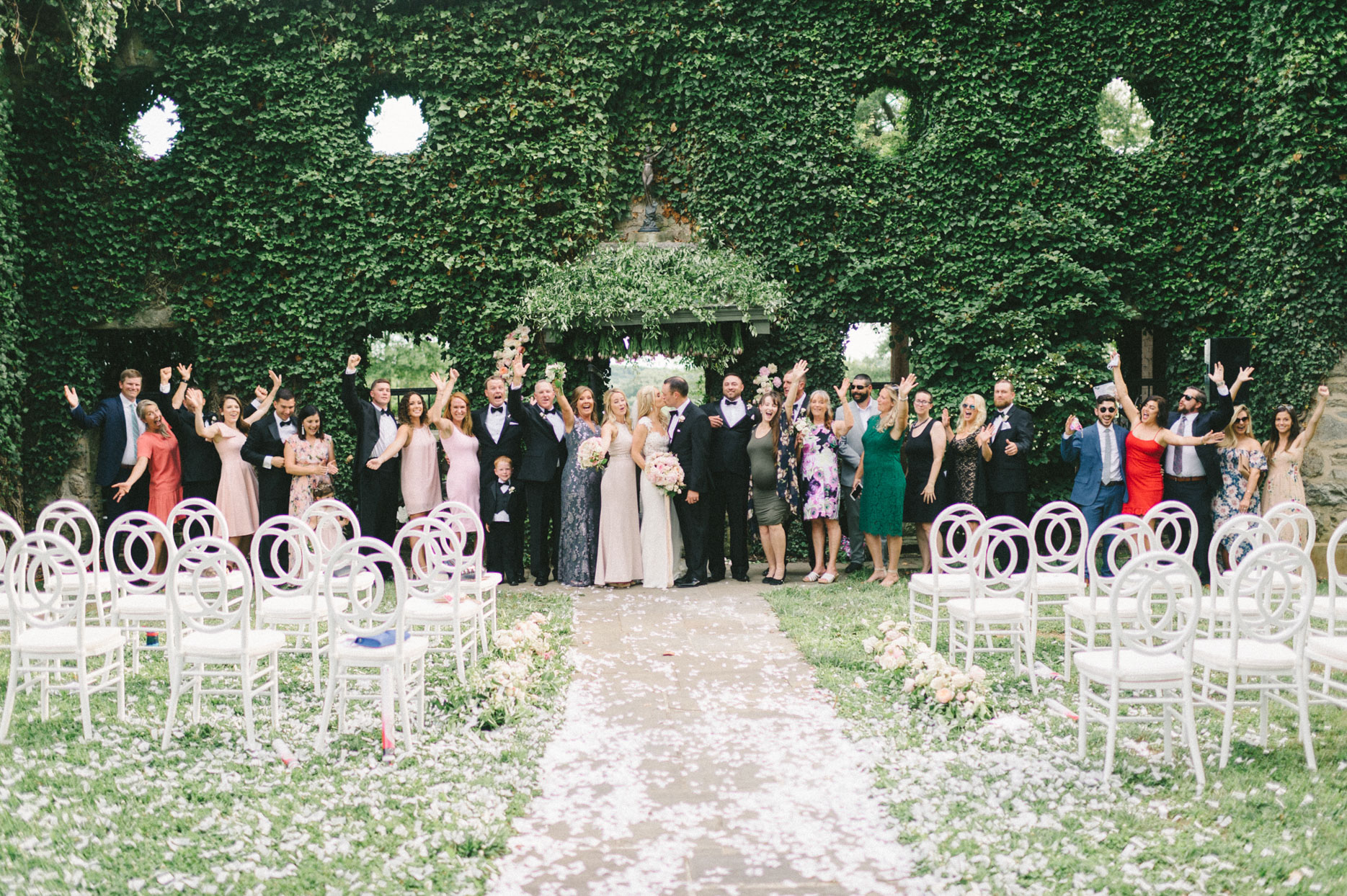 wedding guests group photo in front of greenery wall