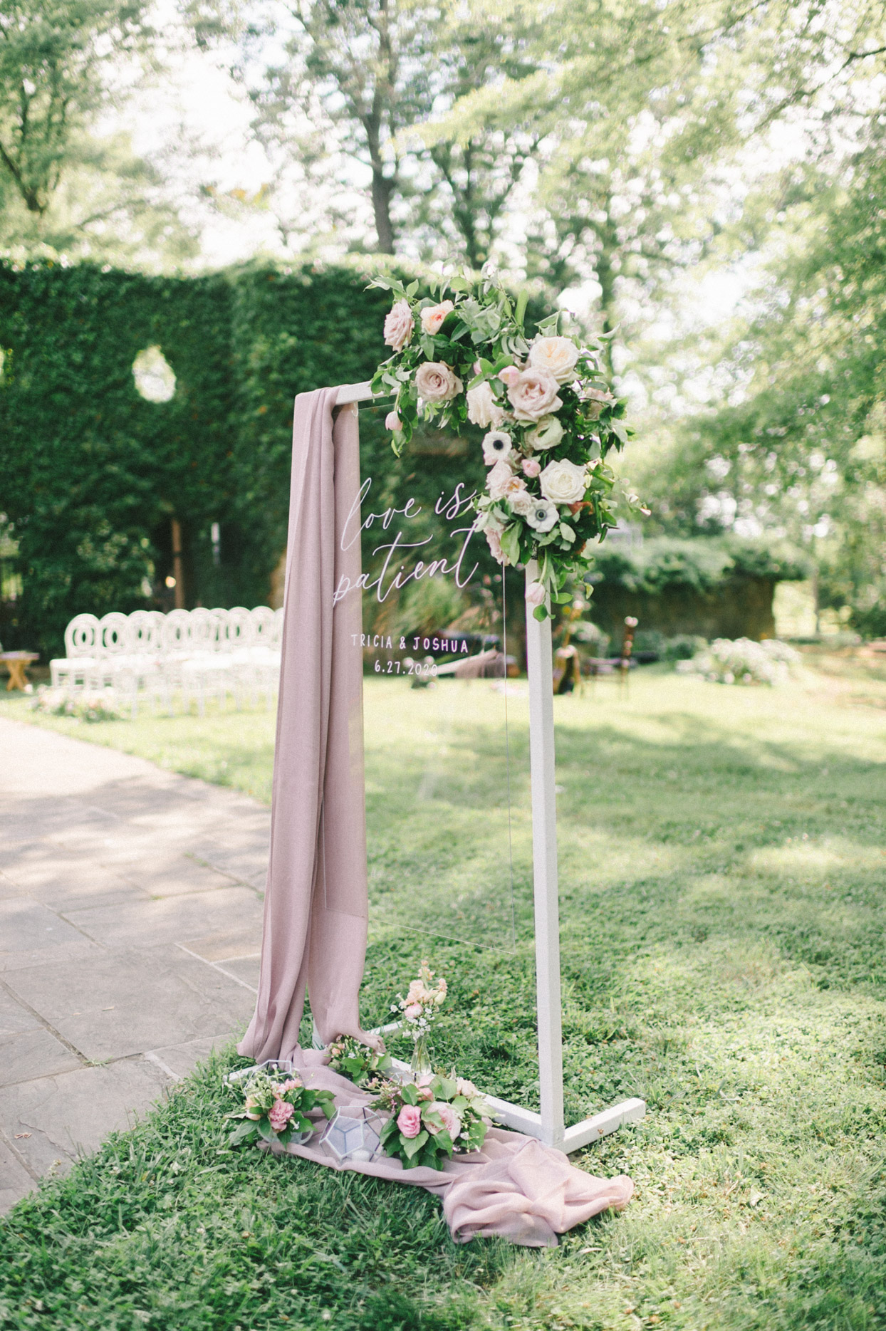 clear wedding sign on grass with mauve drapery