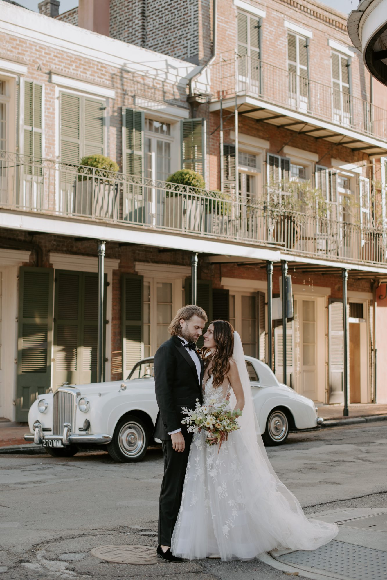 jenny and paul wedding couple posing in the streets of New Orleans in front of vintage car