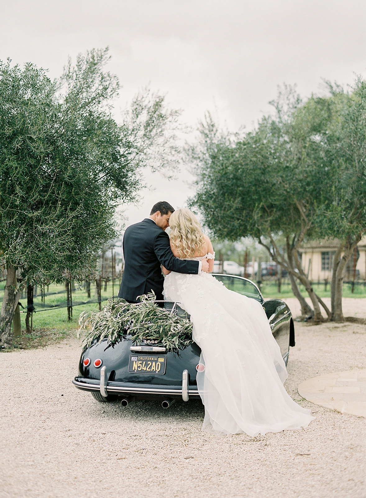bride and groom sitting on black vintage car